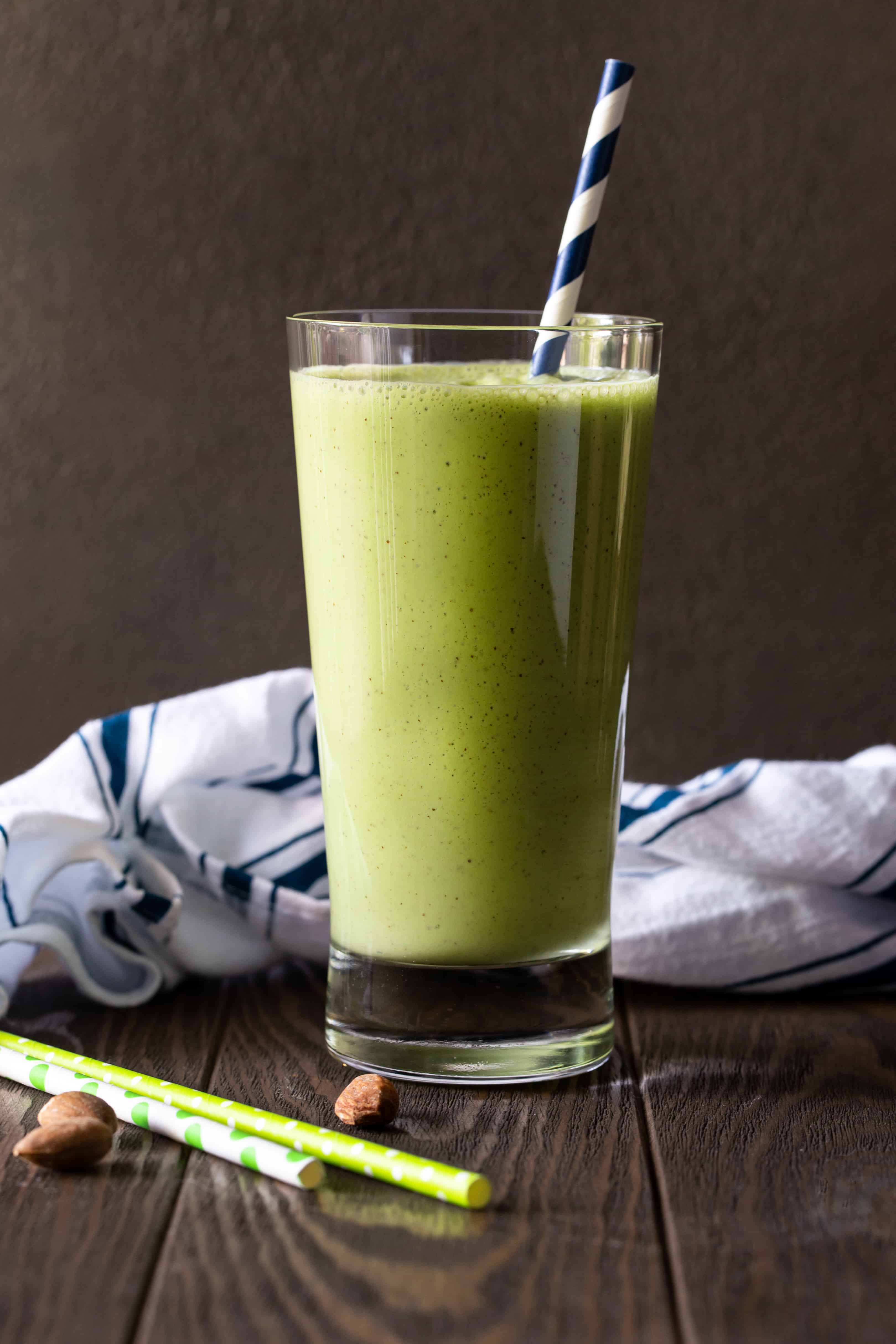 Single glass of blended Banana Spinach Protein Smoothie with a blue and white striped straw.