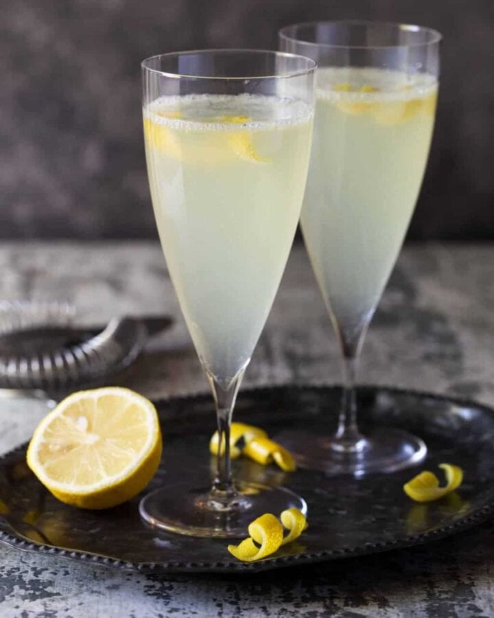 Tall champagne flutes filled with Elderflower French 75 cocktails with lemon slices for garnish.