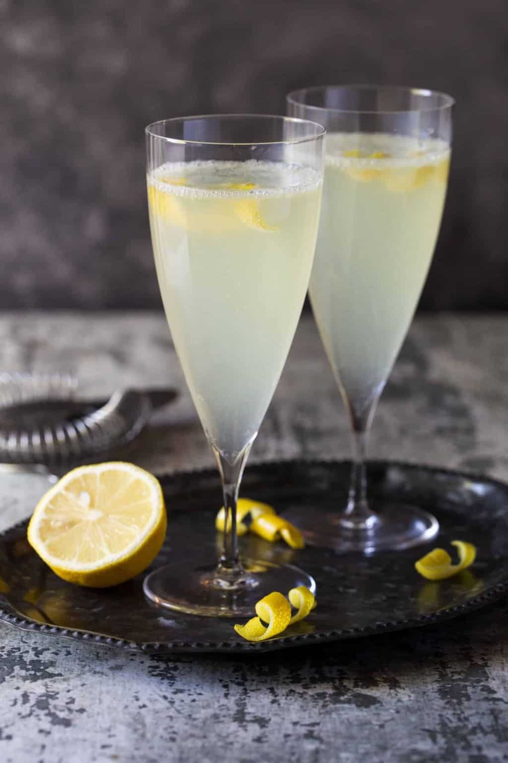 Tall champagne flutes filled with cocktails with lemon slices for garnish.