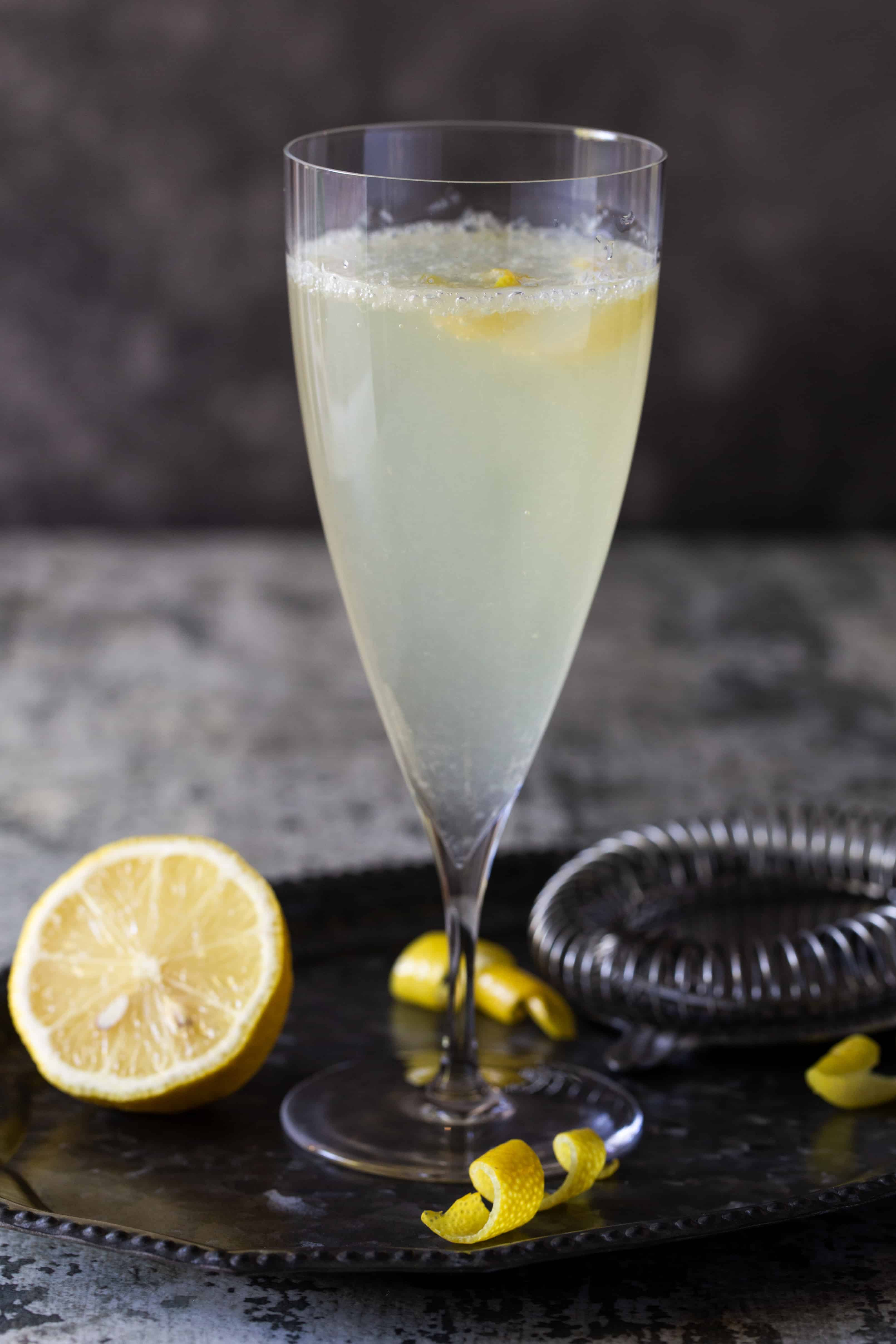 Single Elderflower French 75 cocktail in a tall flute garnished with a lemon slice on a dark background.