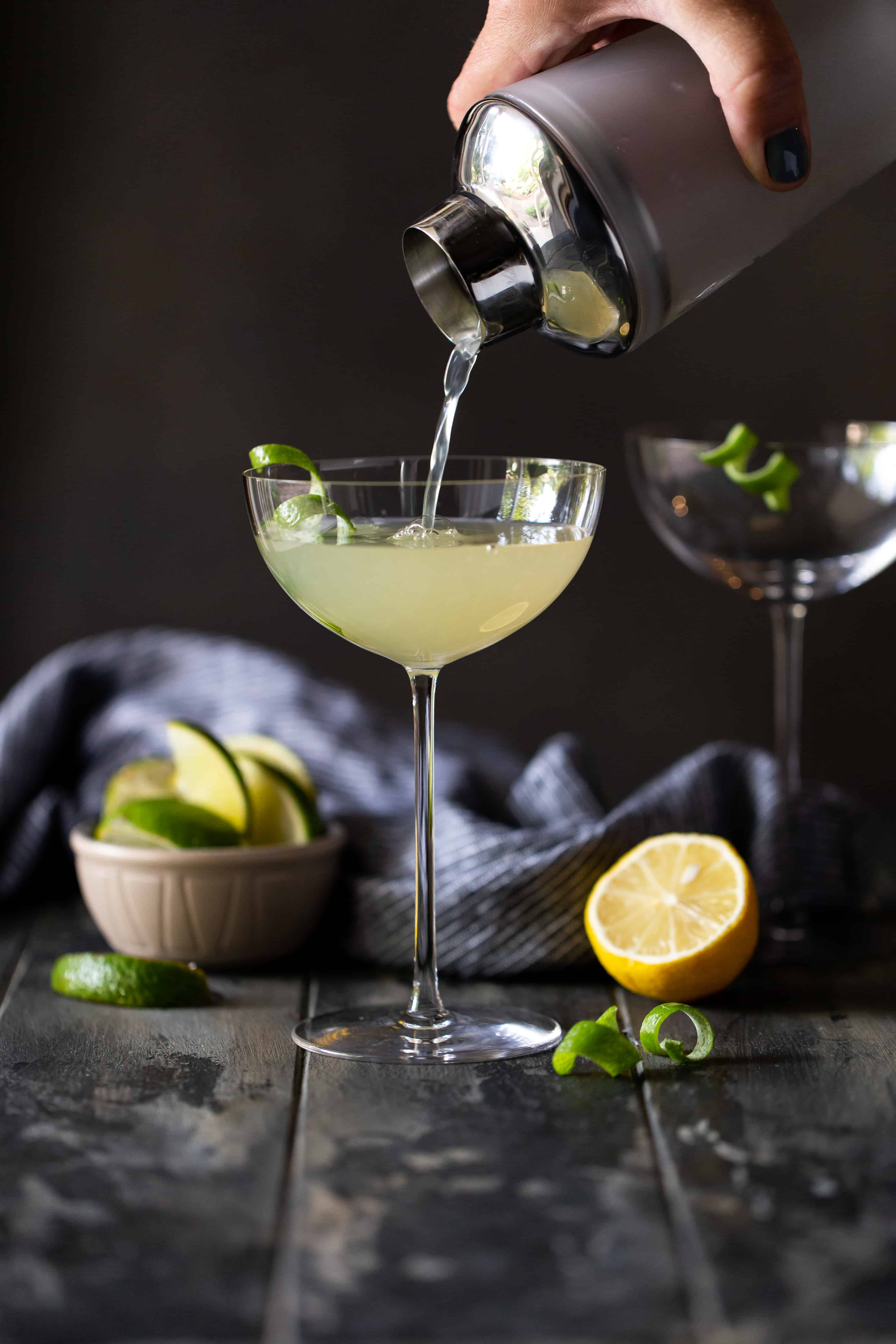 Straight on shot of Elderflower Martini being poured from a shaker into a tall coupe glass with fresh lemon and limes on side.