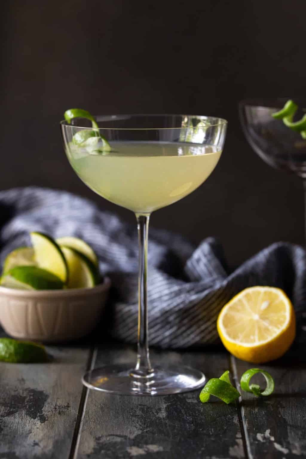 Elderflower martini recipe in tall coupe glass on a dark background with half of a lemon and lime on plate and lime twist for garnish.