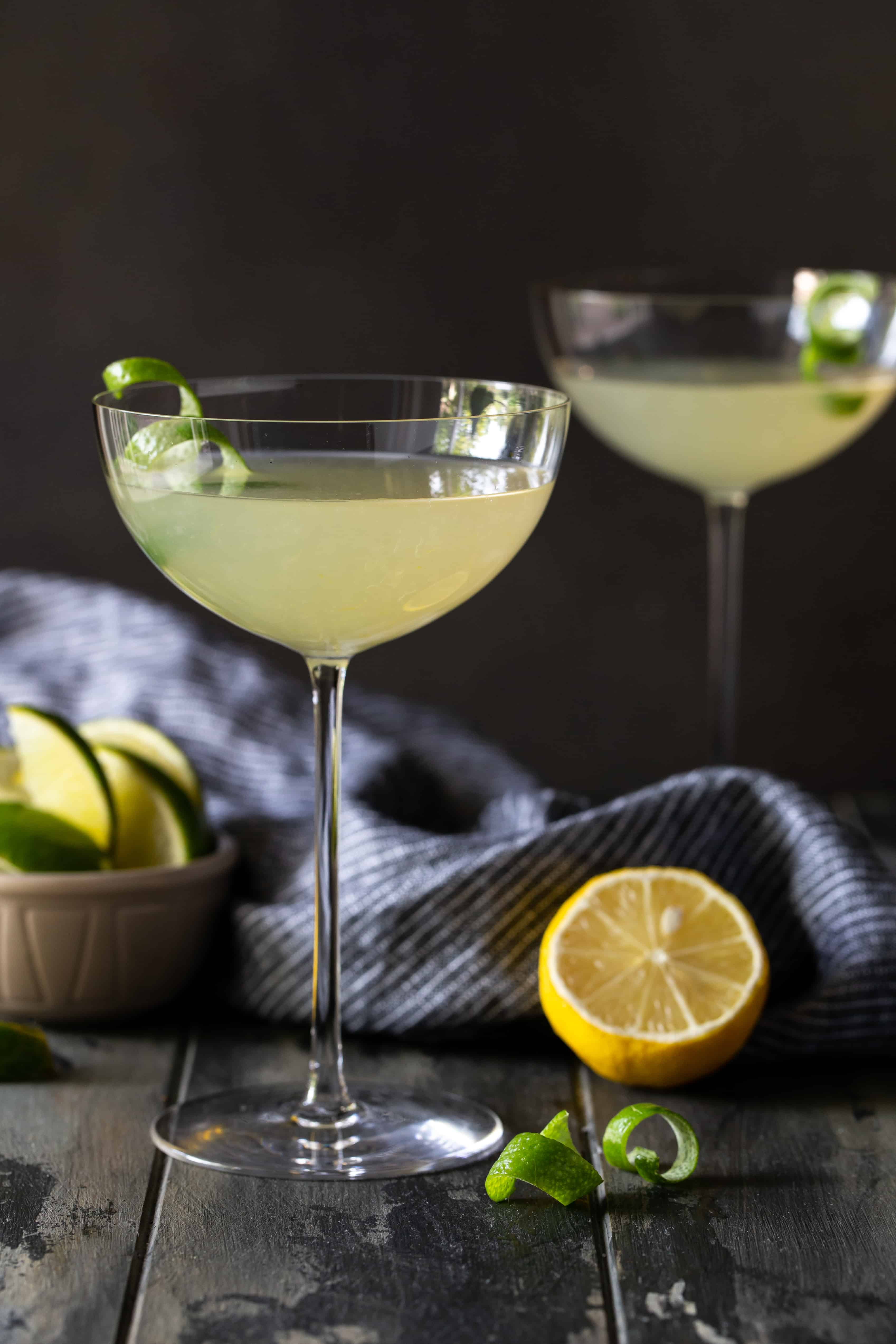 2 elderflower martinis in tall coupe glasses with lime twists for garnish on a dark background.