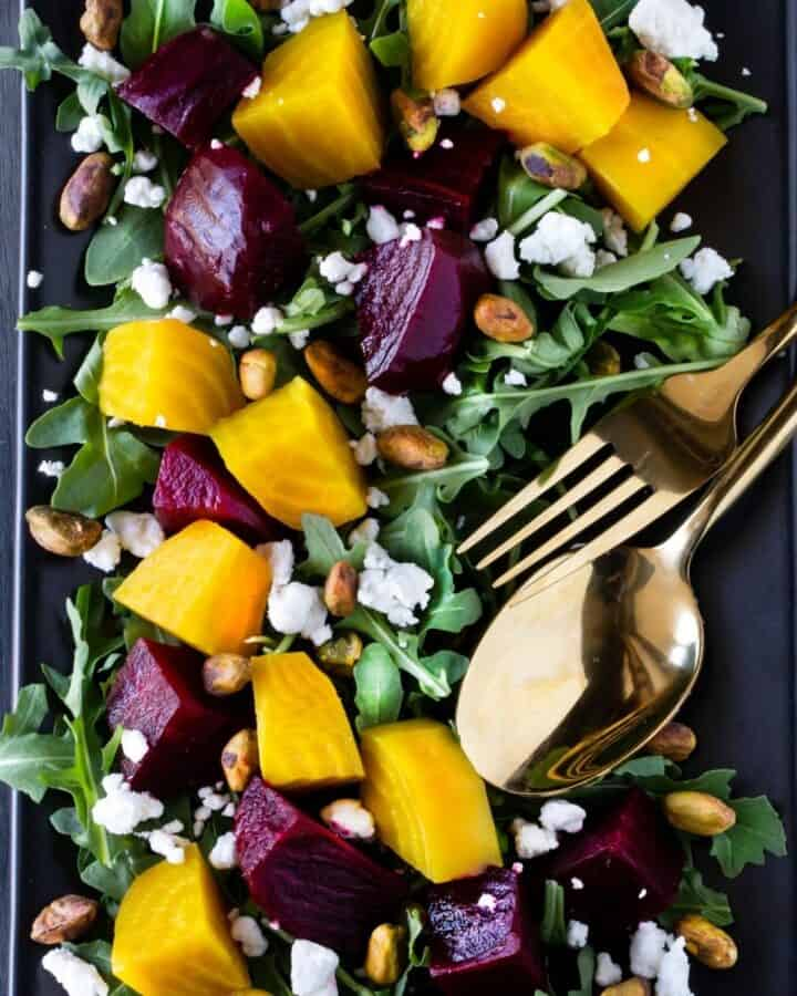 roasted beet salad on plate with fork and spoon.