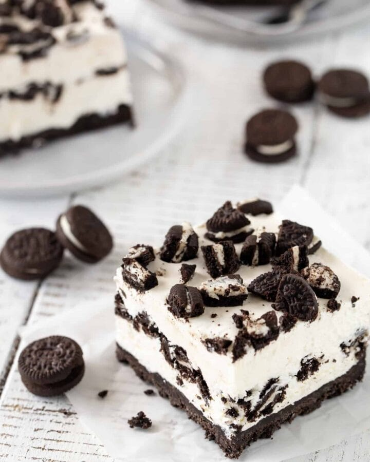 A piece of chocolate cheesecake bar cake on a plate, with Oreos.