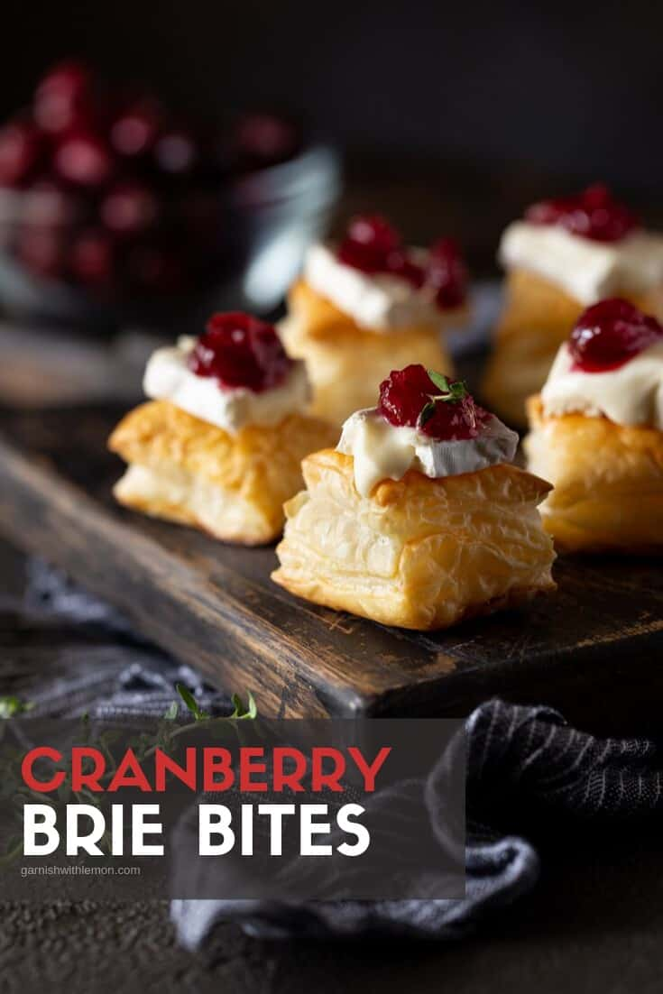 Cranberry Brie Bites on a dark serving board with a linen on the table.