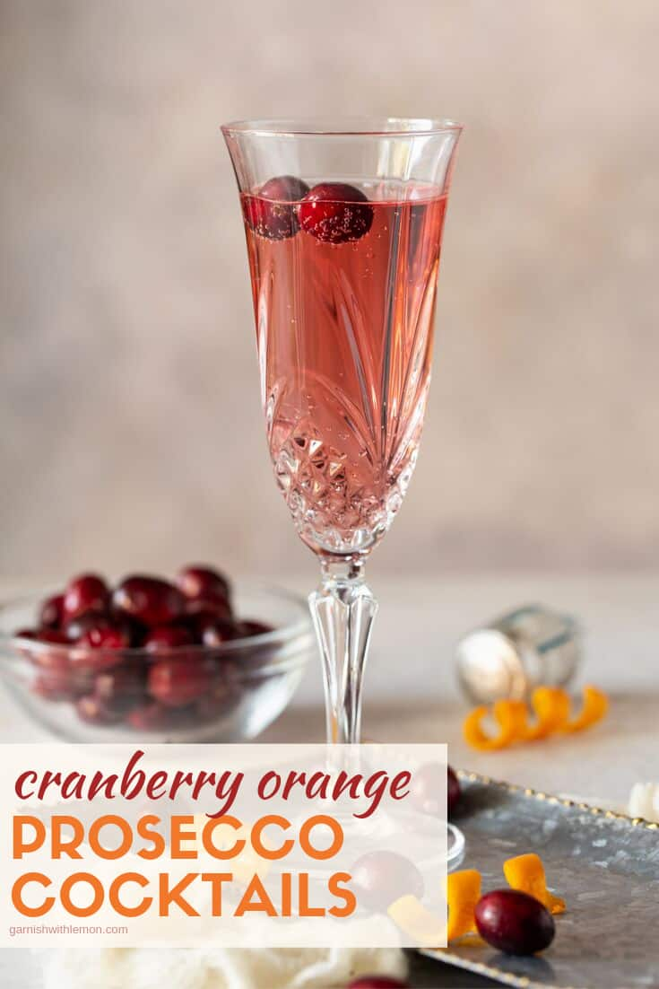 Pinterest image of Cranberry Orange Prosecco Cocktail in a tall champagne flute with fresh cranberries and an orange twist for a garnish.