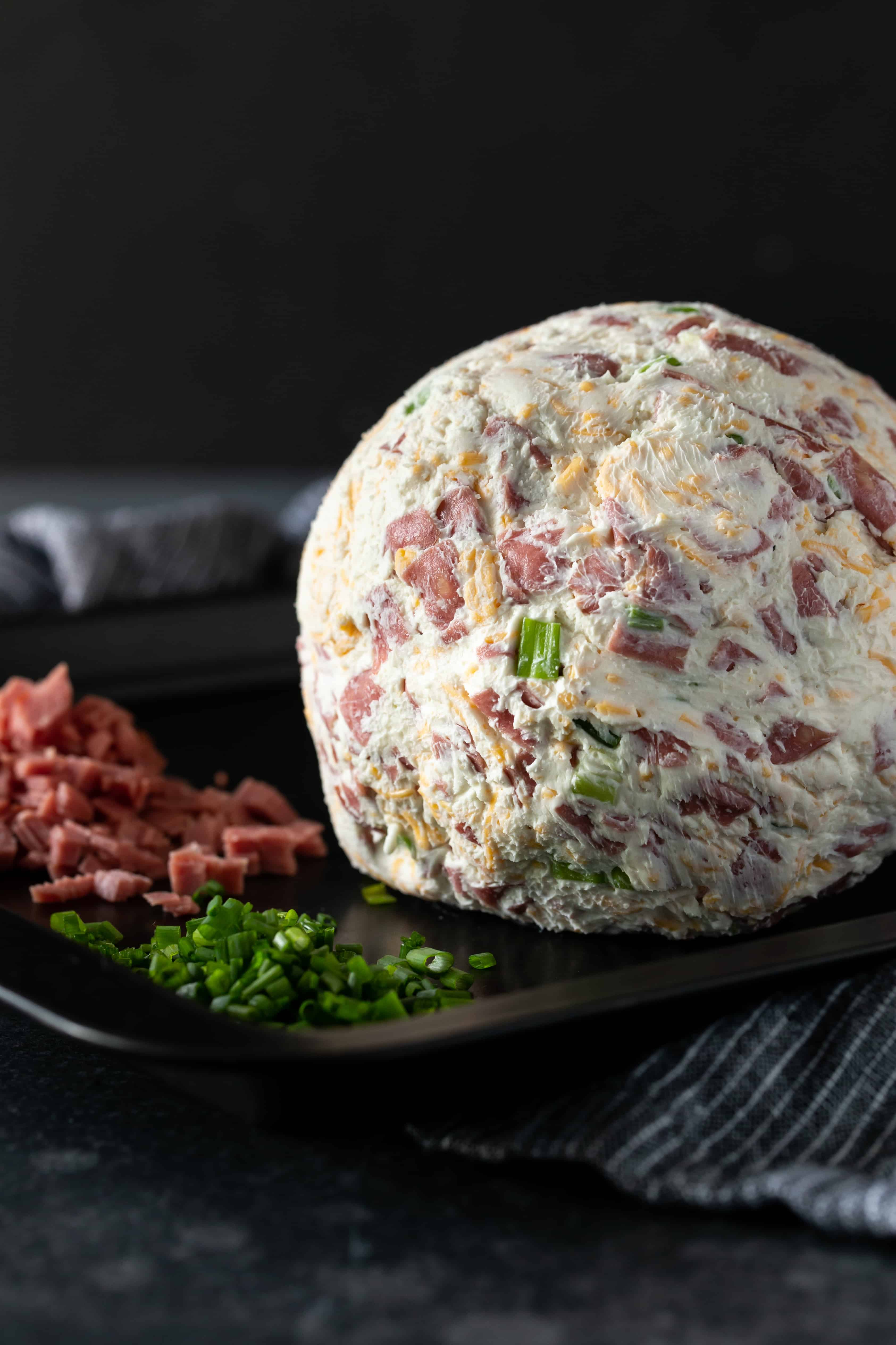 Chipped beef cheese ball that hasn't been rolled in the garnish yest with diced dried beef and chives on a plate ready for rolling.
