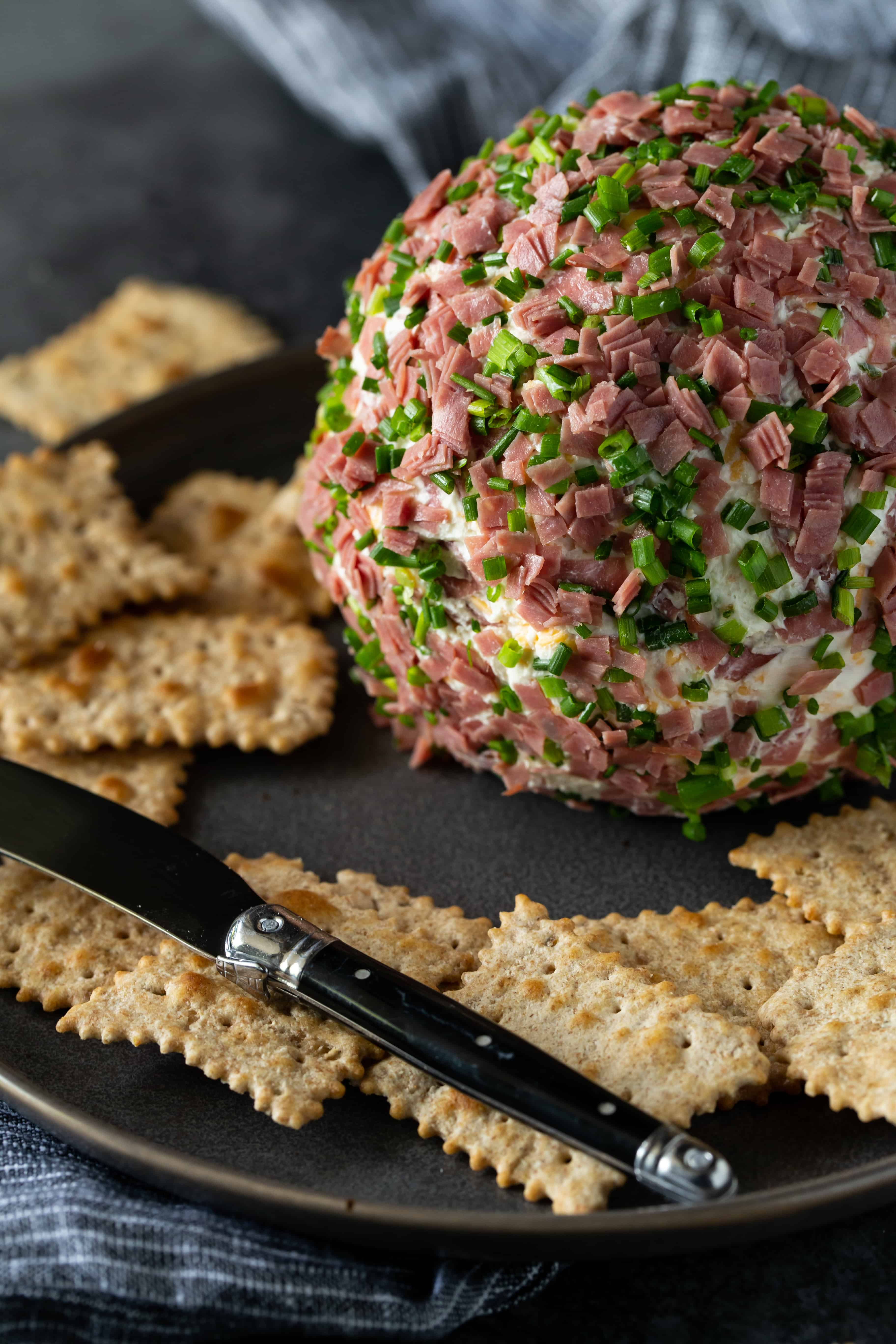 Chipped Beef Cheese ball on a gray plate with black spreader and crackers on the side.