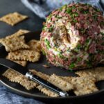 Cheese Ball coated in diced chipped beef and chives on a black plate with crackers and a spreader.