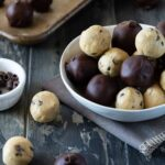 Cookie dough truffles in a white bowl and on a sheet pan. Some dipped in chocolate.
