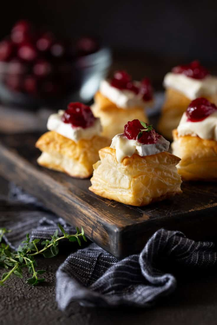 Cranberry Brie Puff pasty bites on a dark background.