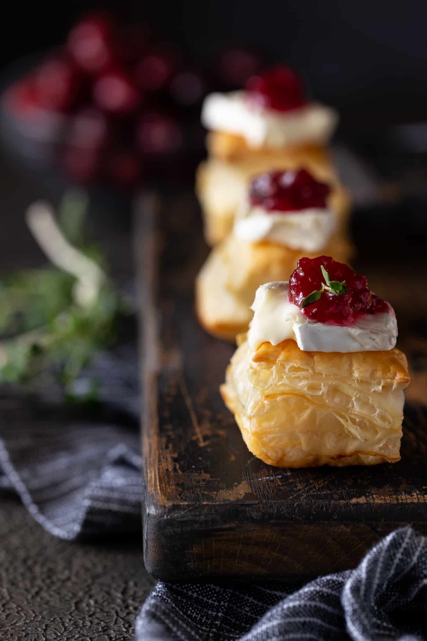 Puff Pastry Bite topped with slice of brie cheese and cranberry sauce and garnished with fresh thyme.