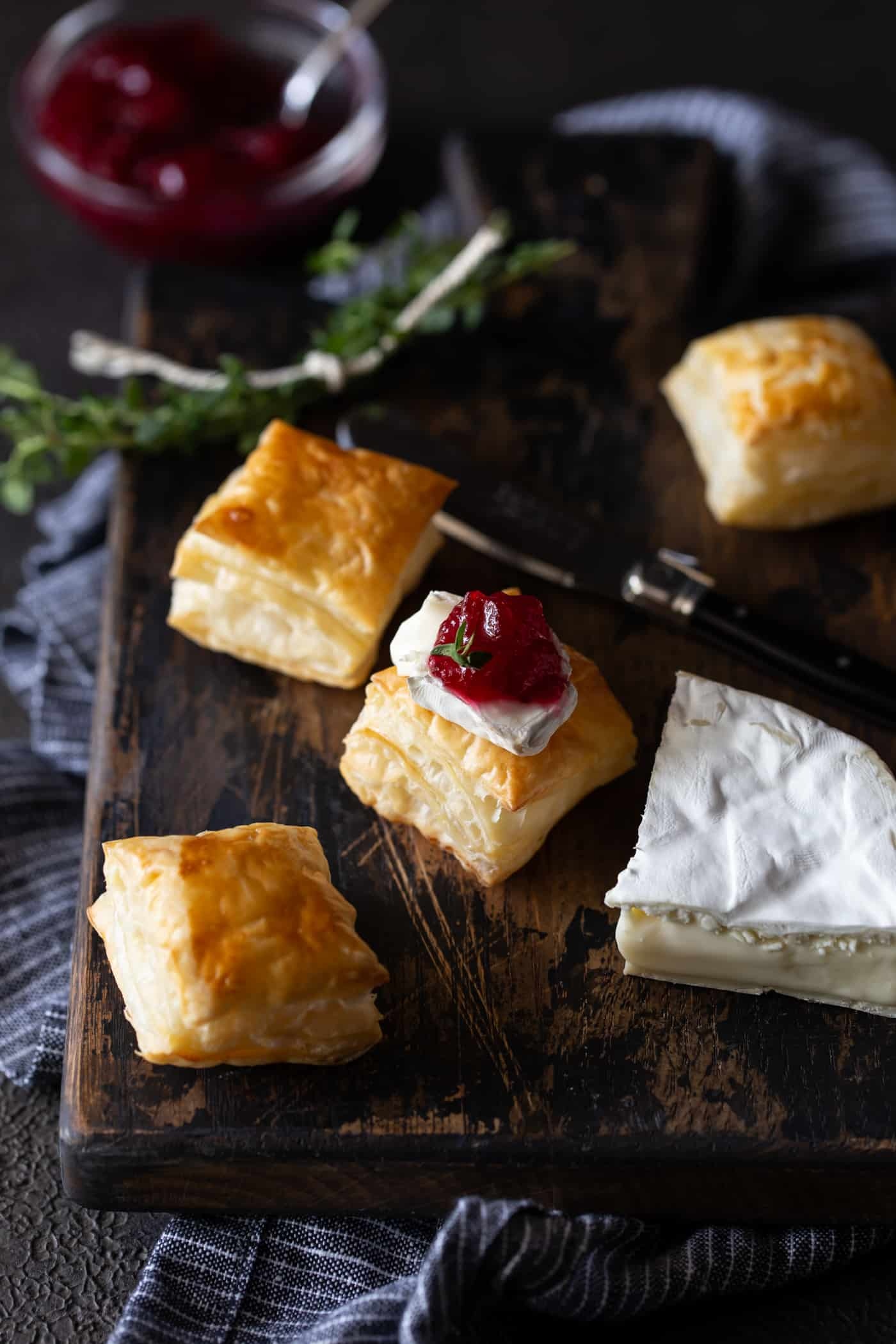 Top down image of brie wedge with puff pastry bites next to it and a bowl of cranberry sauce on a dark background.