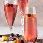 Cranberry Orange Prosecco Cocktails on a silver tray with fresh cranberries and orange peel for garnish.