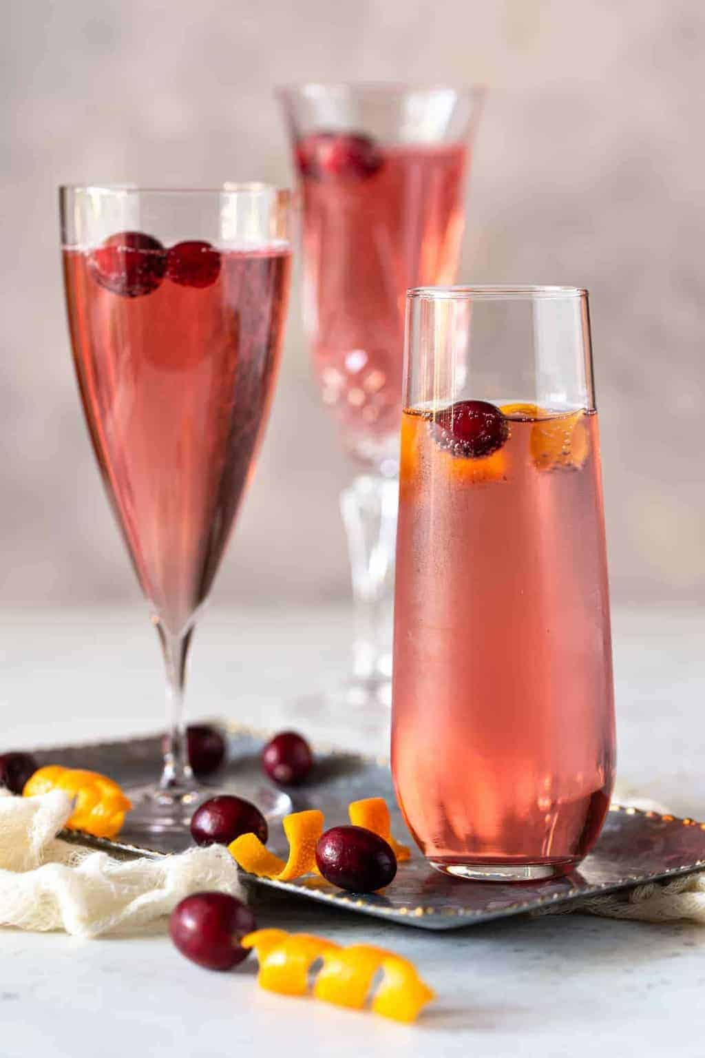 Cranberry Orange Prosecco Cocktails on a silcer tray with fresh cranberries and orange peel for garnish.