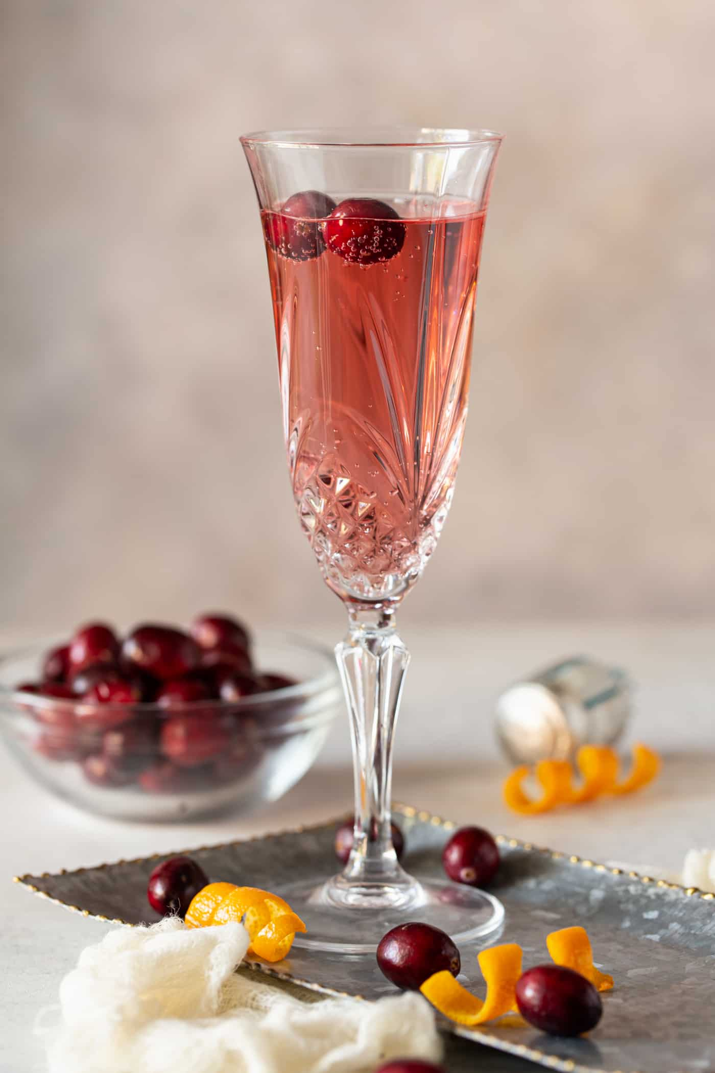 Single glass of Cranberry Orange Prosecco Cocktail in a chapgane flute with fresh cranberries and oranges for garnish.