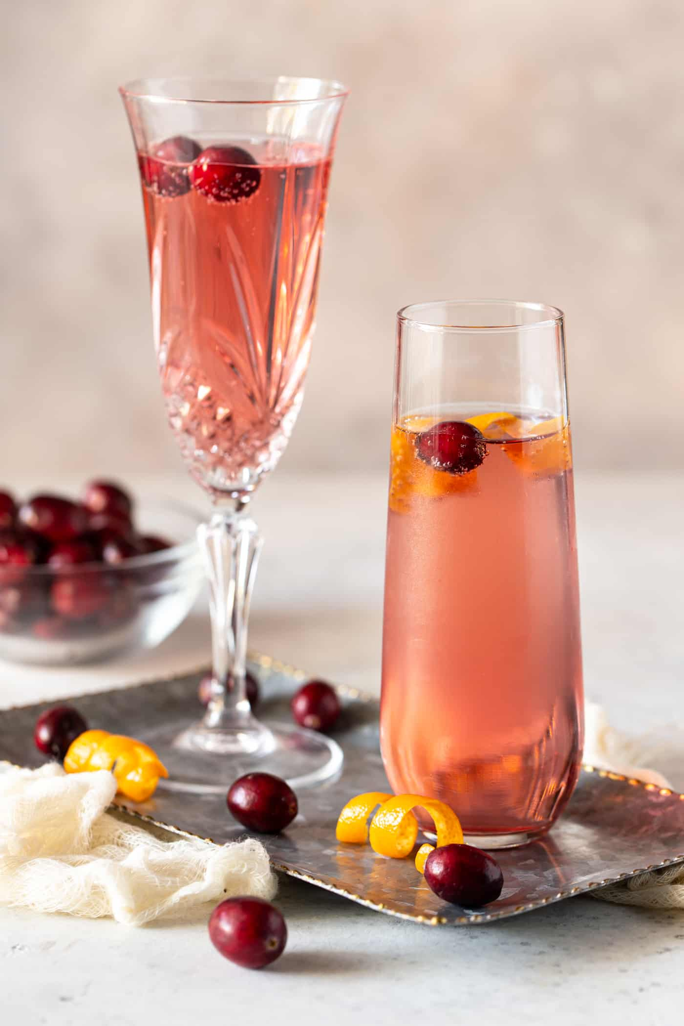 Cocktails in champagne flutes on a silver tray with fresh cranberries for garnish.