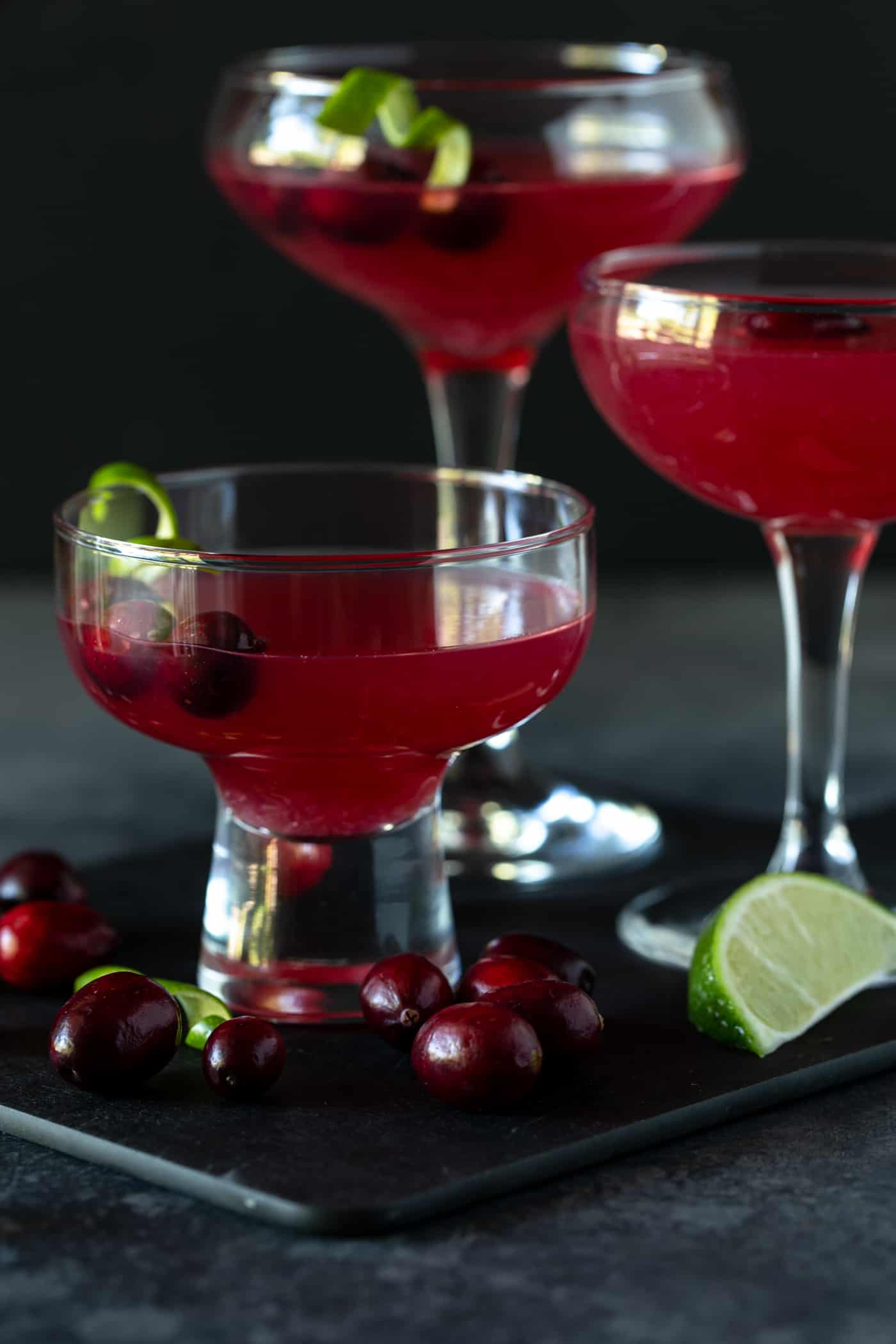Three different coupe glasses filled with Cranberry Vodka Gimlet cocktails. Garnished with fresh lime and cranberries.