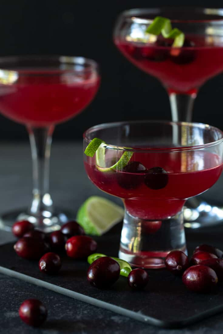 Coupe and martini glasses filled with Cranberry Vodka Gimlet Cocktails and garnished with lime twists and fresh cranberries.