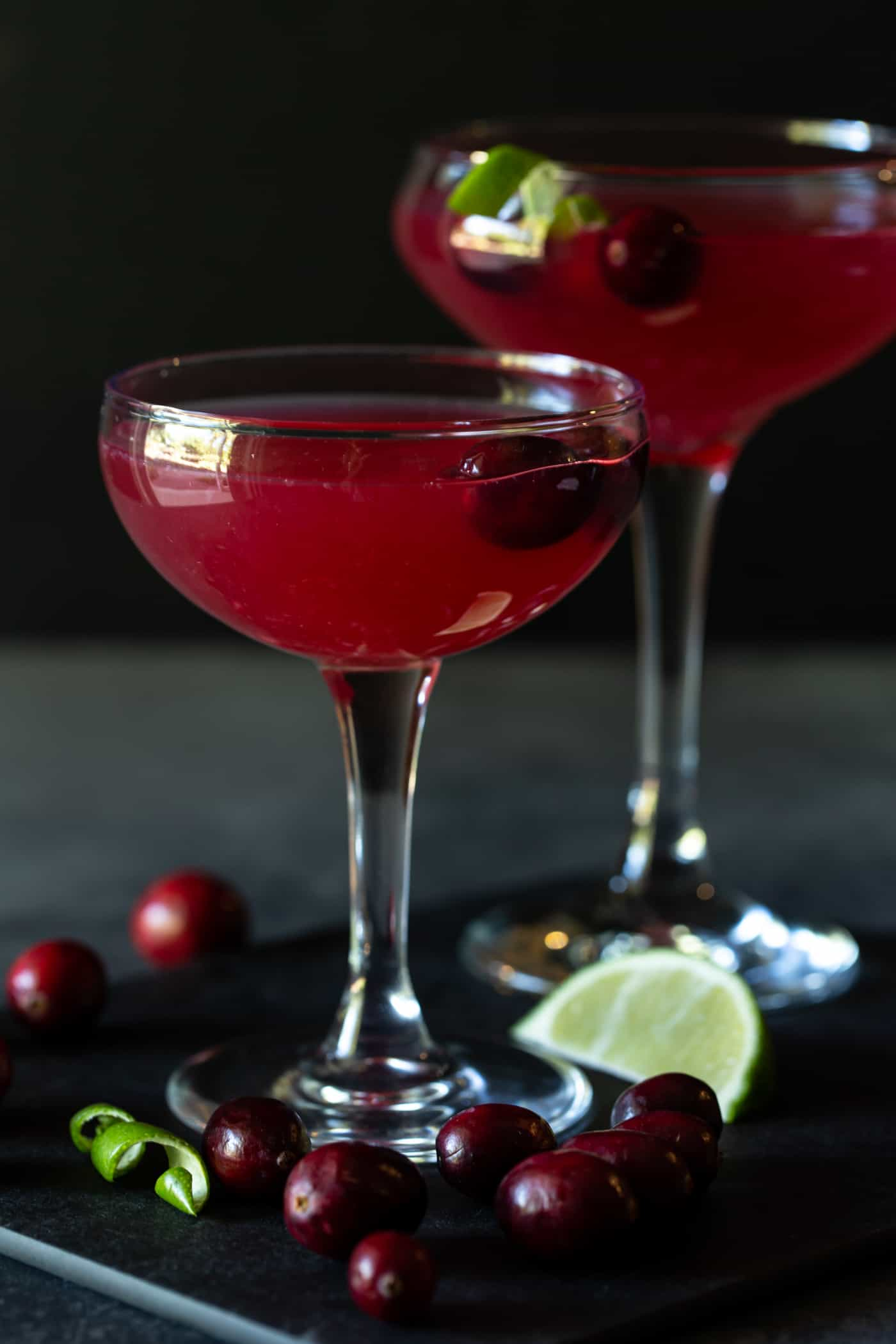 Two Cranberry Vodka Gimlets in coupe glasses garnished with lime twists and fresh cranberries.