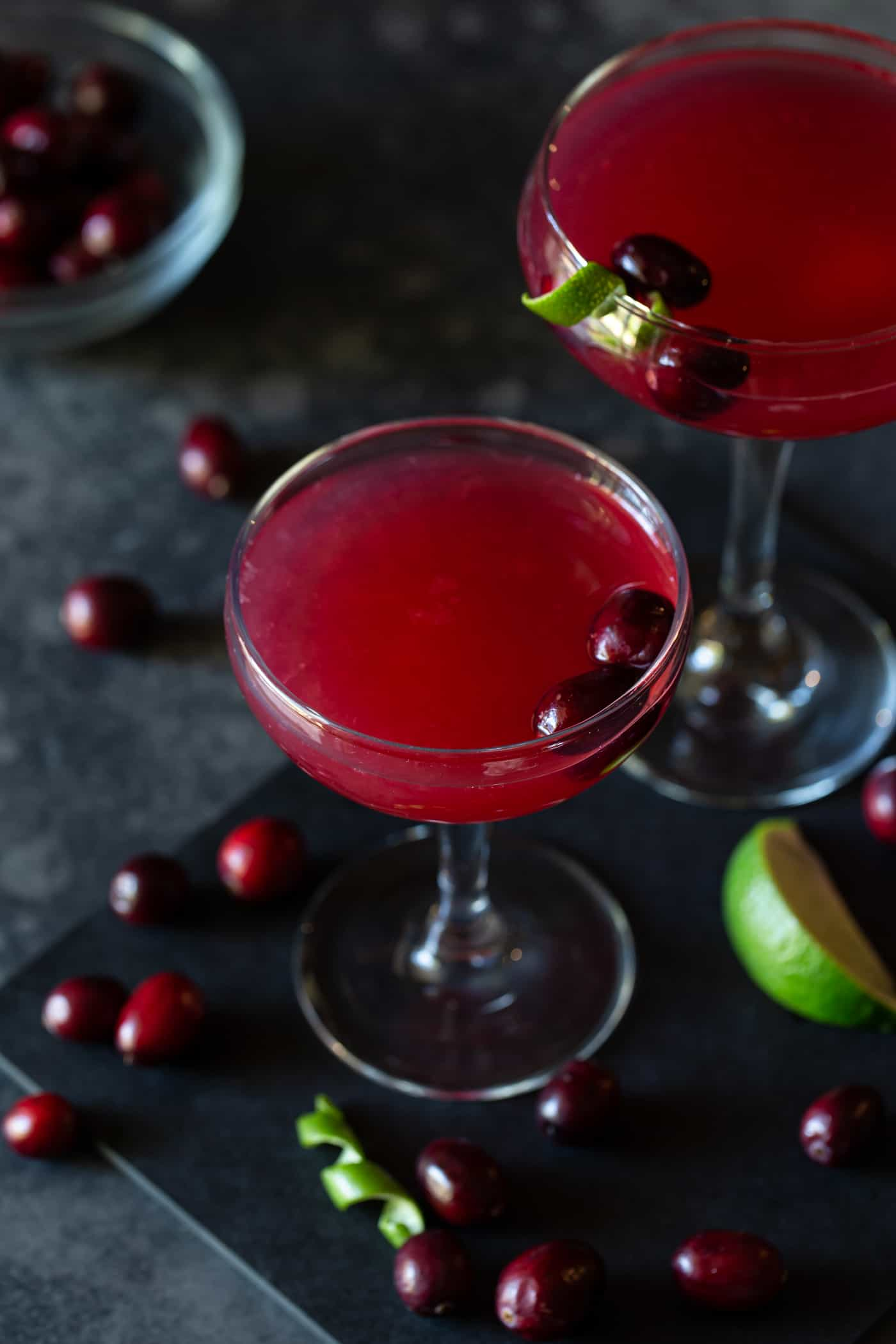 Two coupe glasses filled with Cranberry Vodka Gimlet Cocktails. Garnished with additional cranberries and fresh lime rind twists.