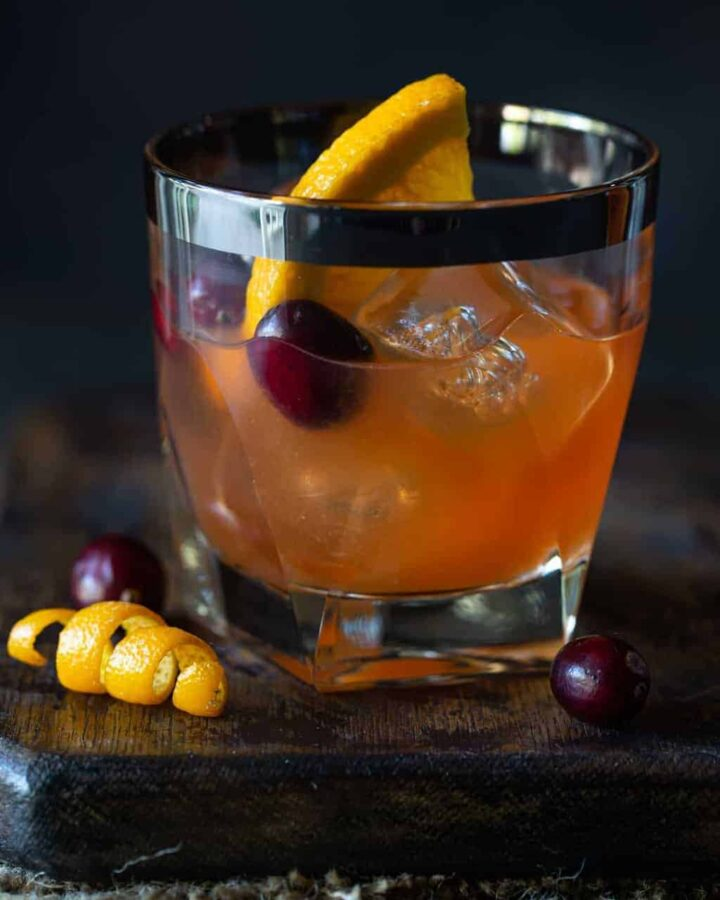 a single lowball glass of Cranberry Whiskey Sour Cocktail. Garnished with fresh cranberries, an orange twist and a fresh orange slice.