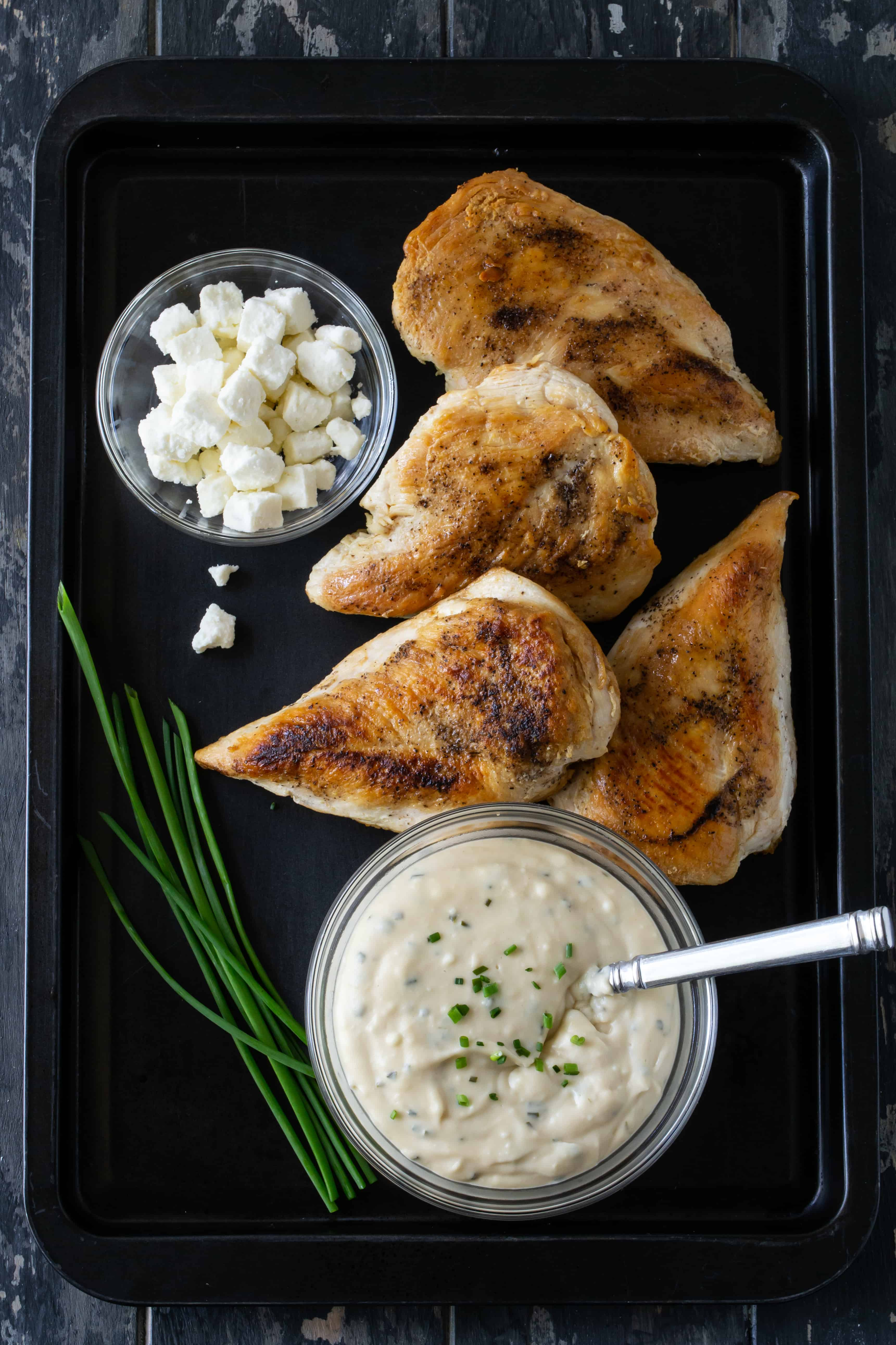 Feta Chicken recipe ingredients on a black sheet pan, including seared chicken breasts, fresh feta cheese chunks, feta cheese sauce and fresh chives.