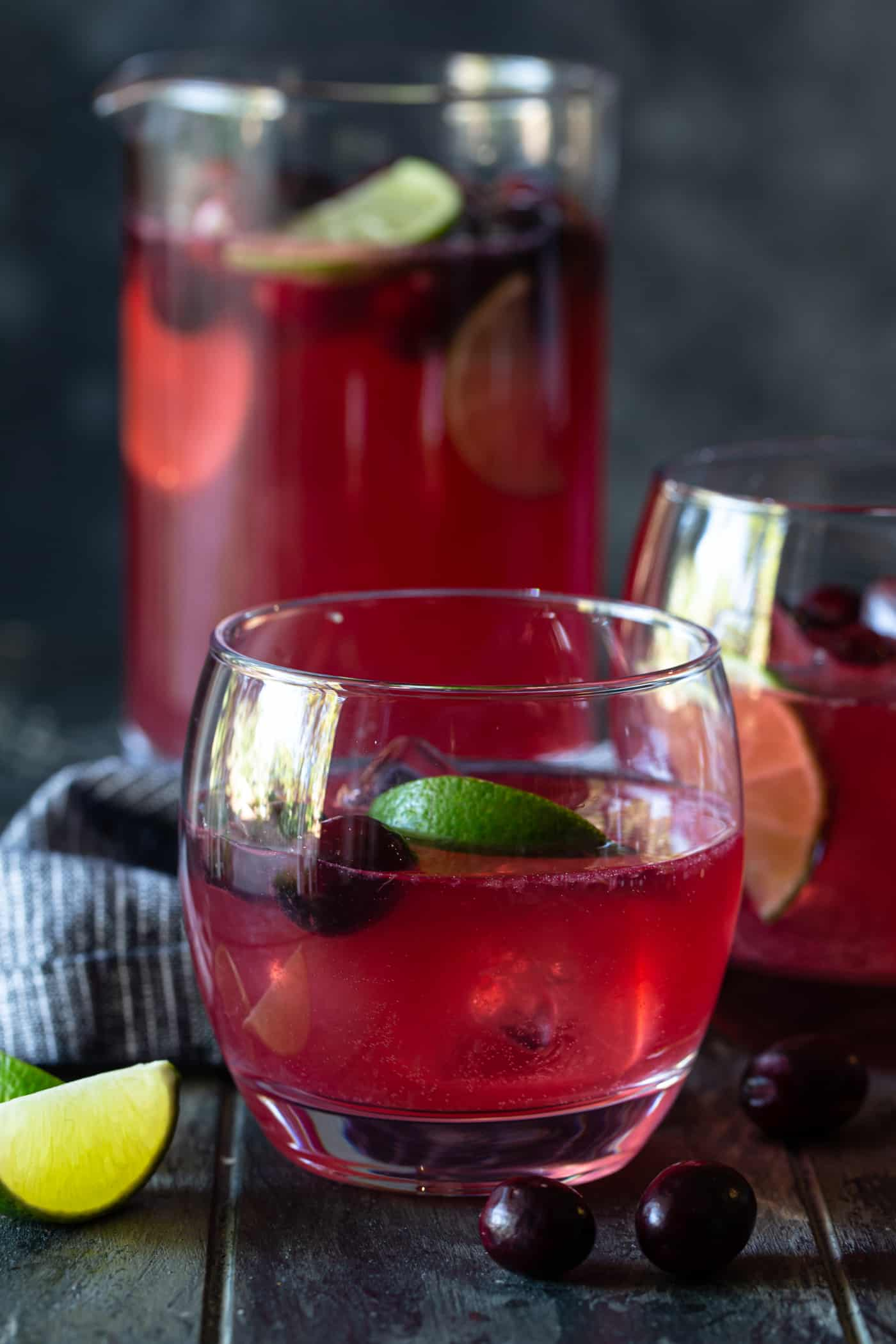 A pitcher and low ball glass filled with Punch and garnished with fresh lime wedges and fresh cranberries.