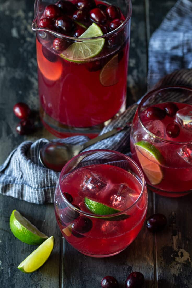 Pitcher filled with Cranberry Vodka Party punch that is garnished with fresh cranberries and lime slices and surrounded by lowball glasses filled with punch.