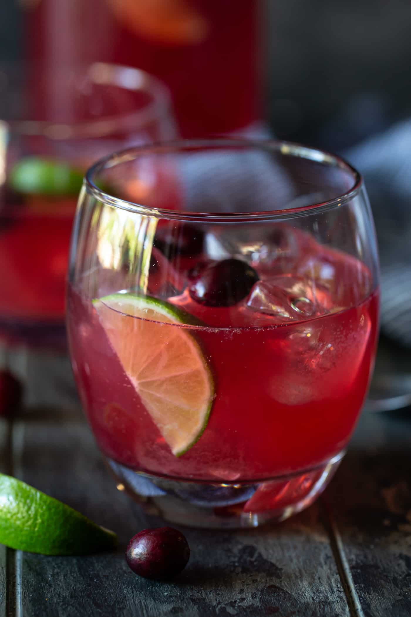 Low ball glass filled with Cranberry Vodka Party Punch. Glass is garnished with fresh cranberries and lime slices.