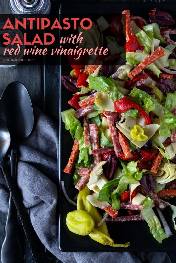 Pinterest image of Antipasto Salad with red wine vinaigrette on a gray platter with a large spoons for serving.