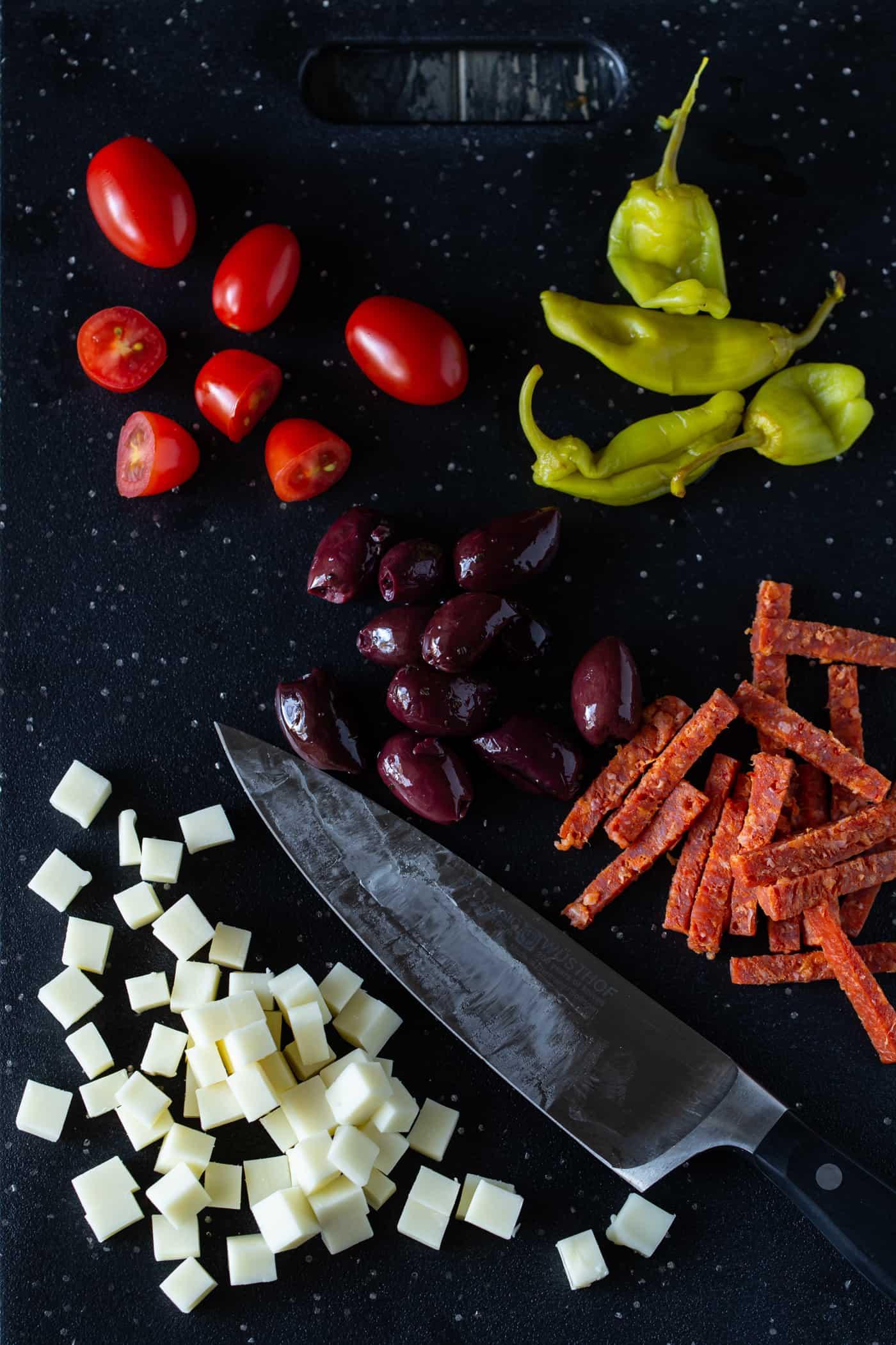 Ingredient shot of antipasto salad on a dark cutting board.