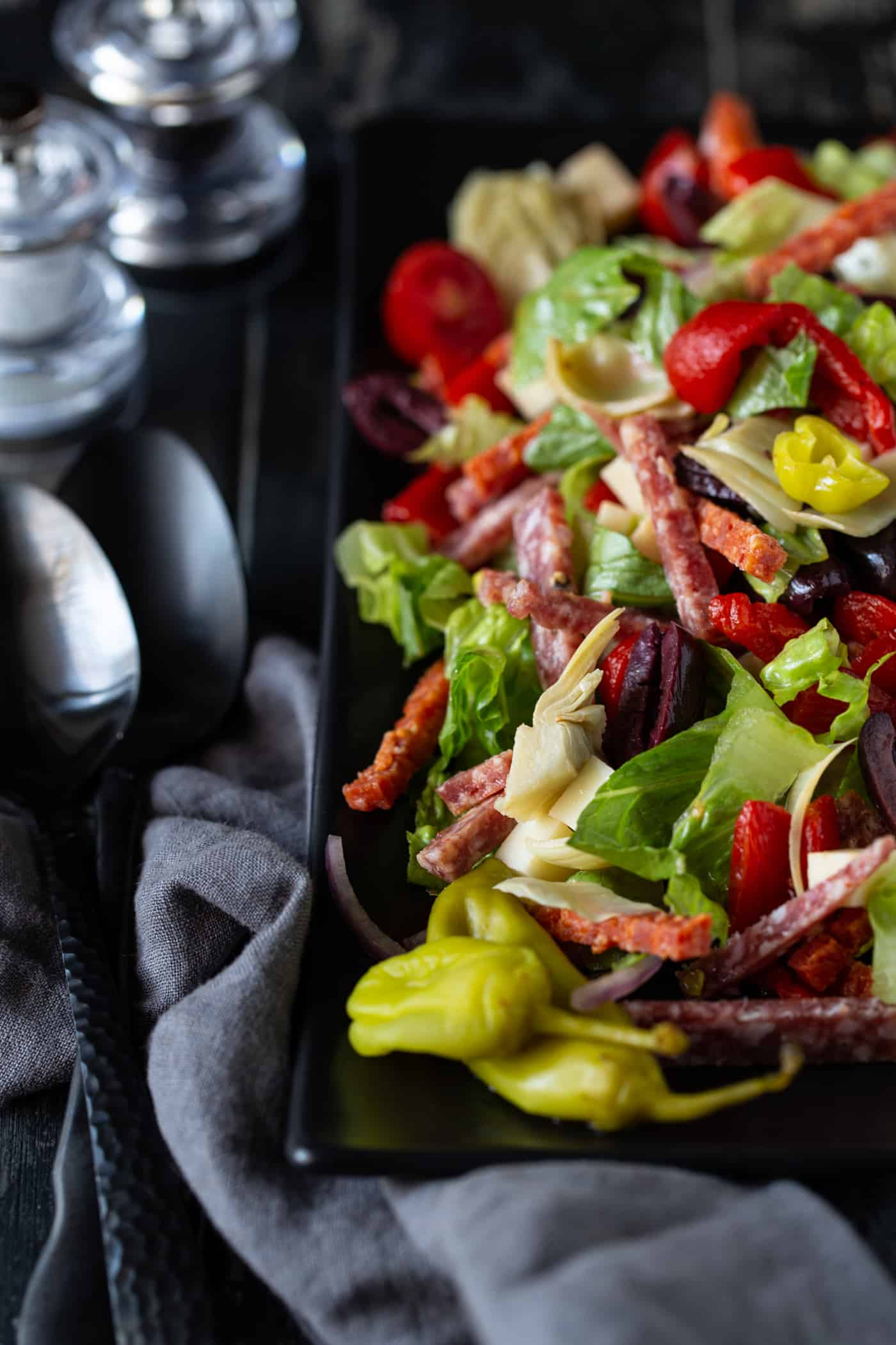 Top down image of Antipasto Salad with Red wine vinaigrette on a dark plate with a spoon for serving.