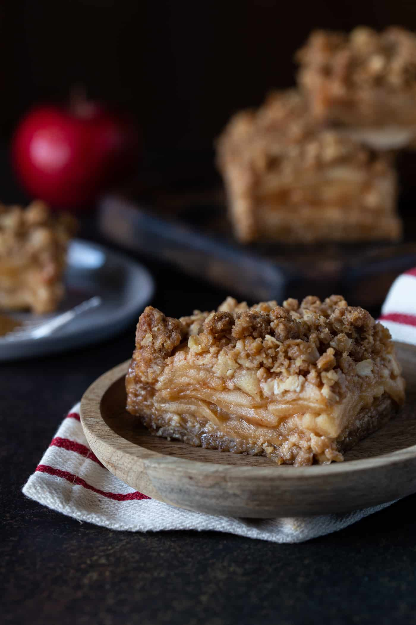 Apple Crisp Bars stacked on a wooden cutting board with a single bar on a wood plate in the front.