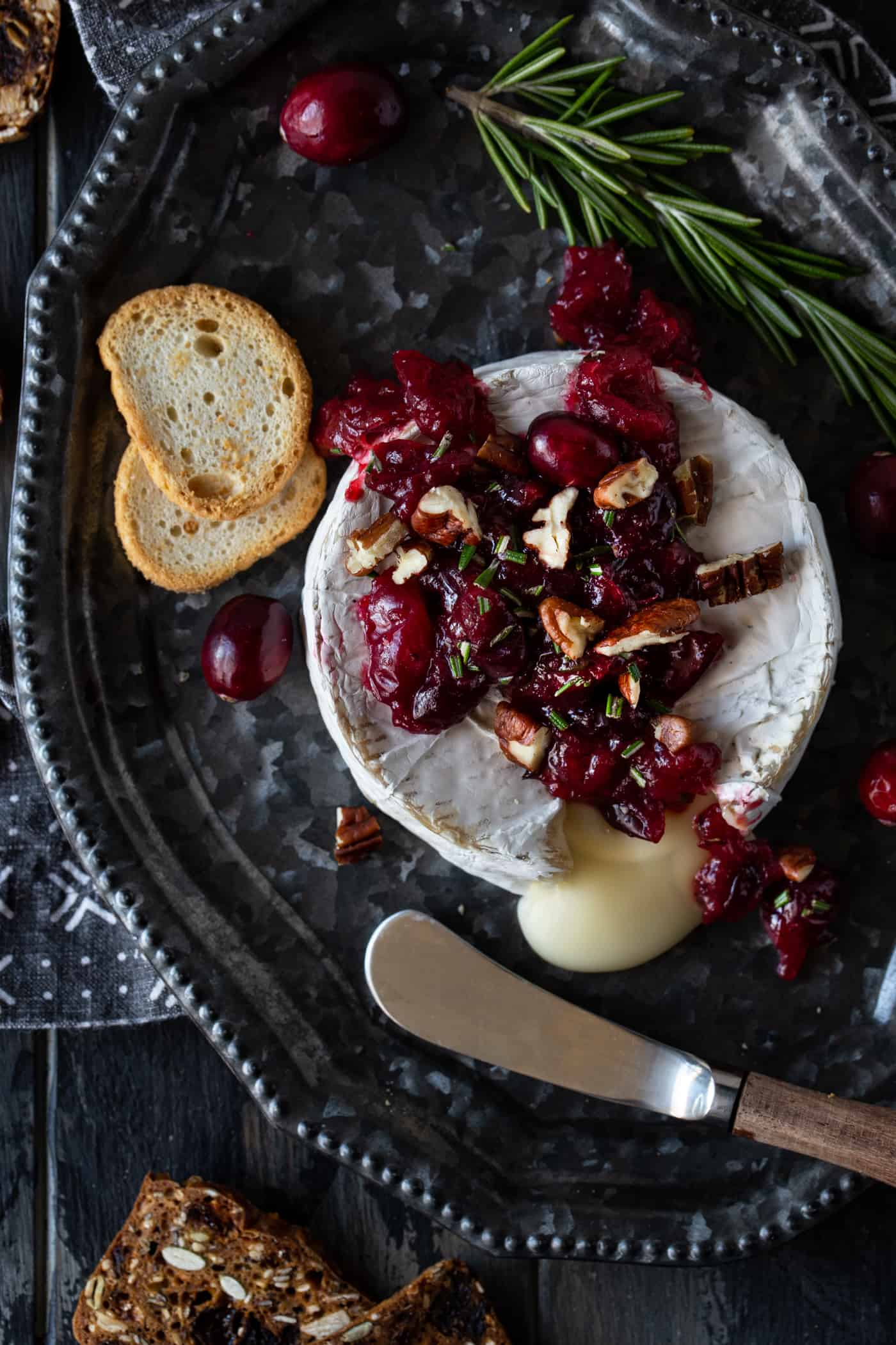 A wheel of warm brie with Cranberries and Pecans on a silver tray with a spreader and mini toasts.