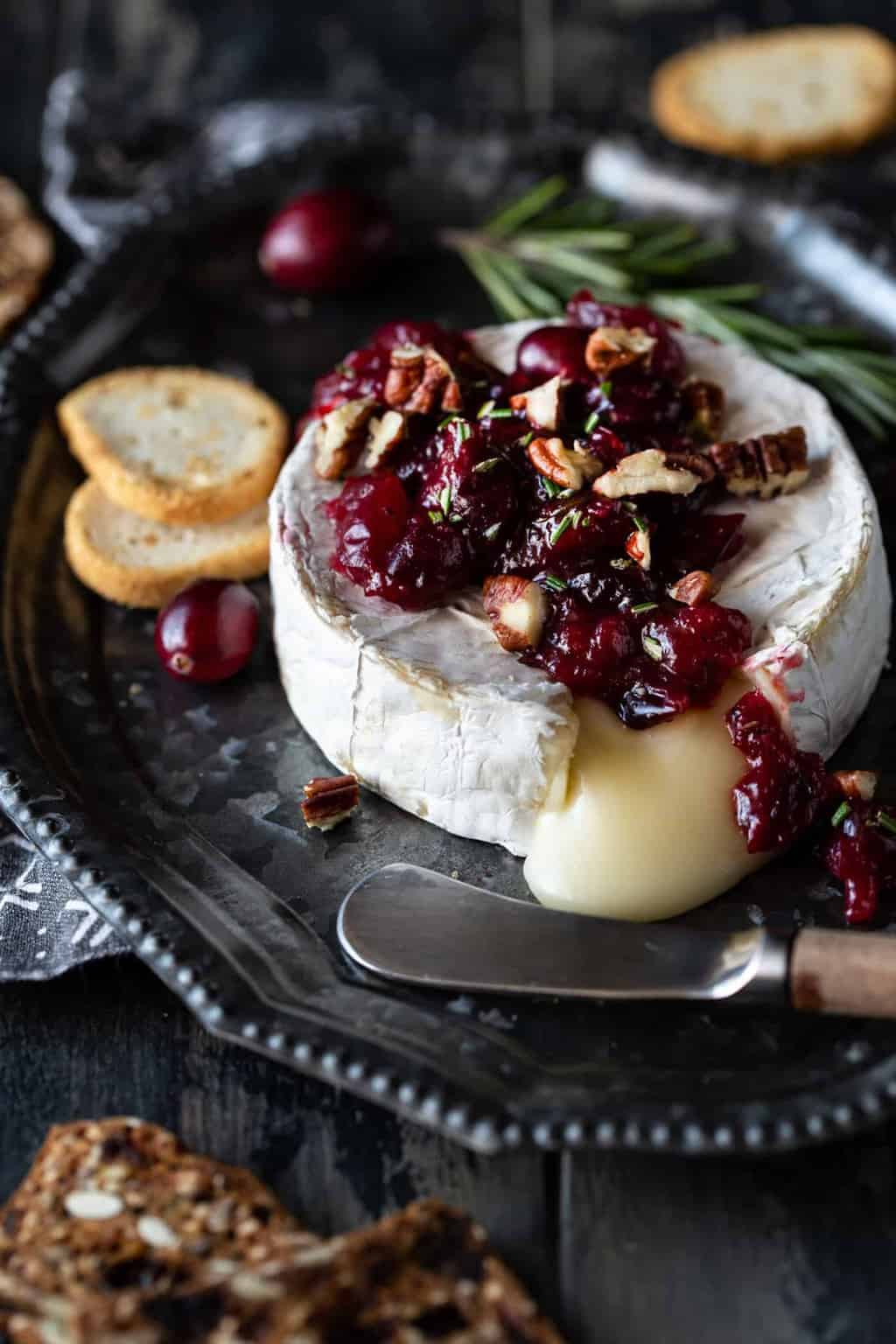 Wheel of baked brie with cranberries and pecans on a silver tray.