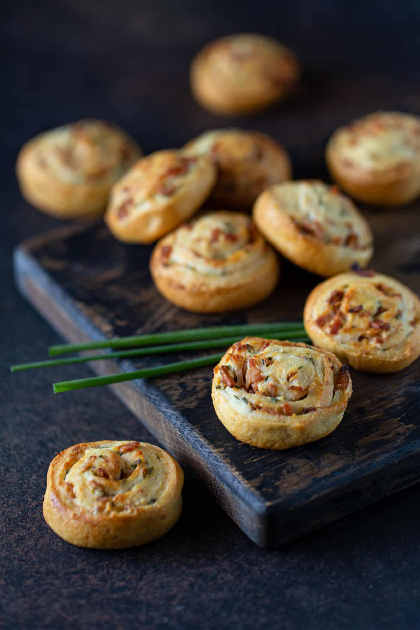 Bacon Cream Cheese Crescent Roll Appetizers on a dark wooden cutting board. Garnished with fresh chives.