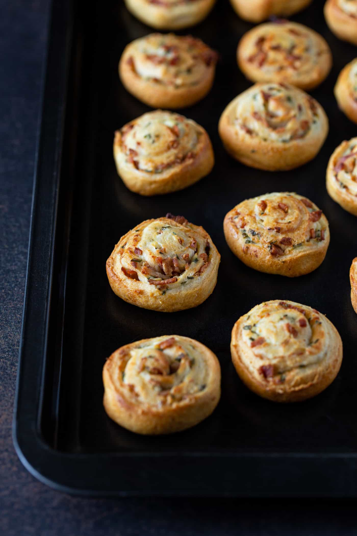 Bacon Cream Cheese Crescent Roll Appetizers on a dark metal sheet pan.