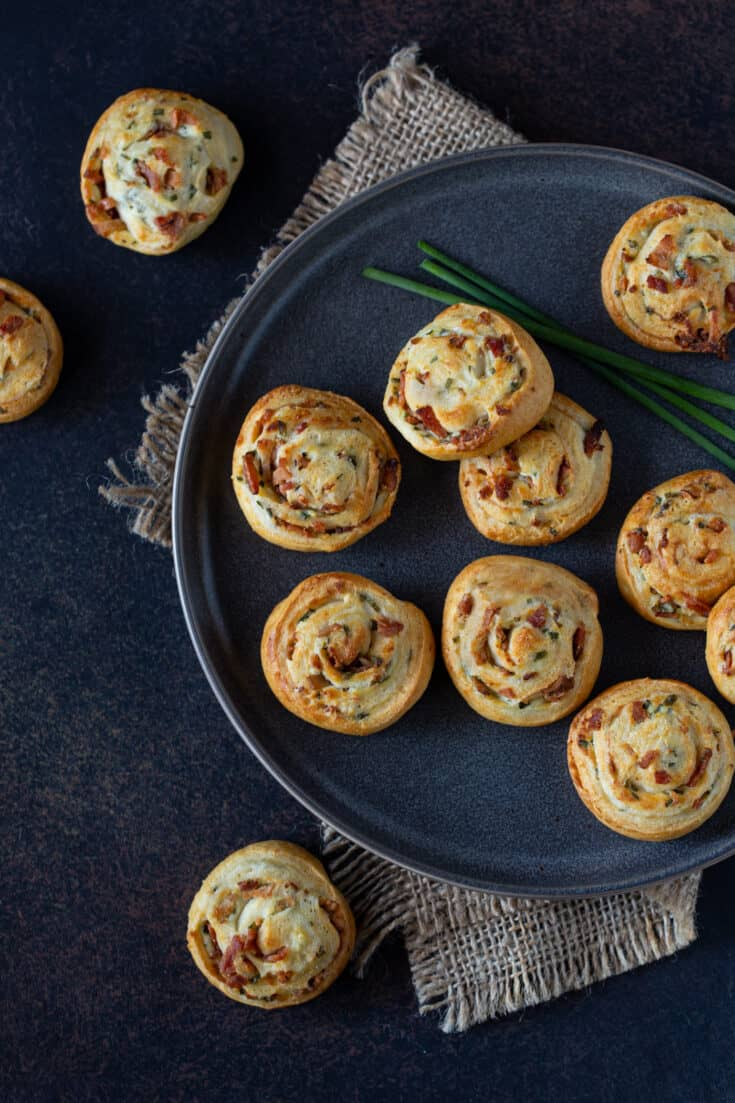 Bacon Cream Cheese Crescent Roll Appetizers on a dark gray plate. Garnished with fresh chives.