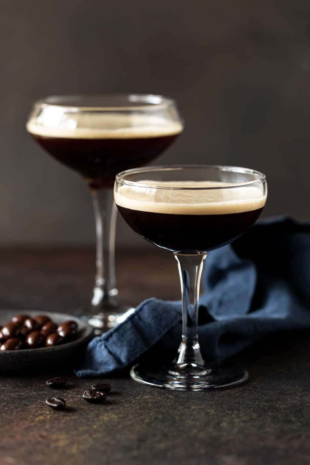 2 Espresso martinis in coupe glasses with frothy tops and chocolate covered espresso beans.
