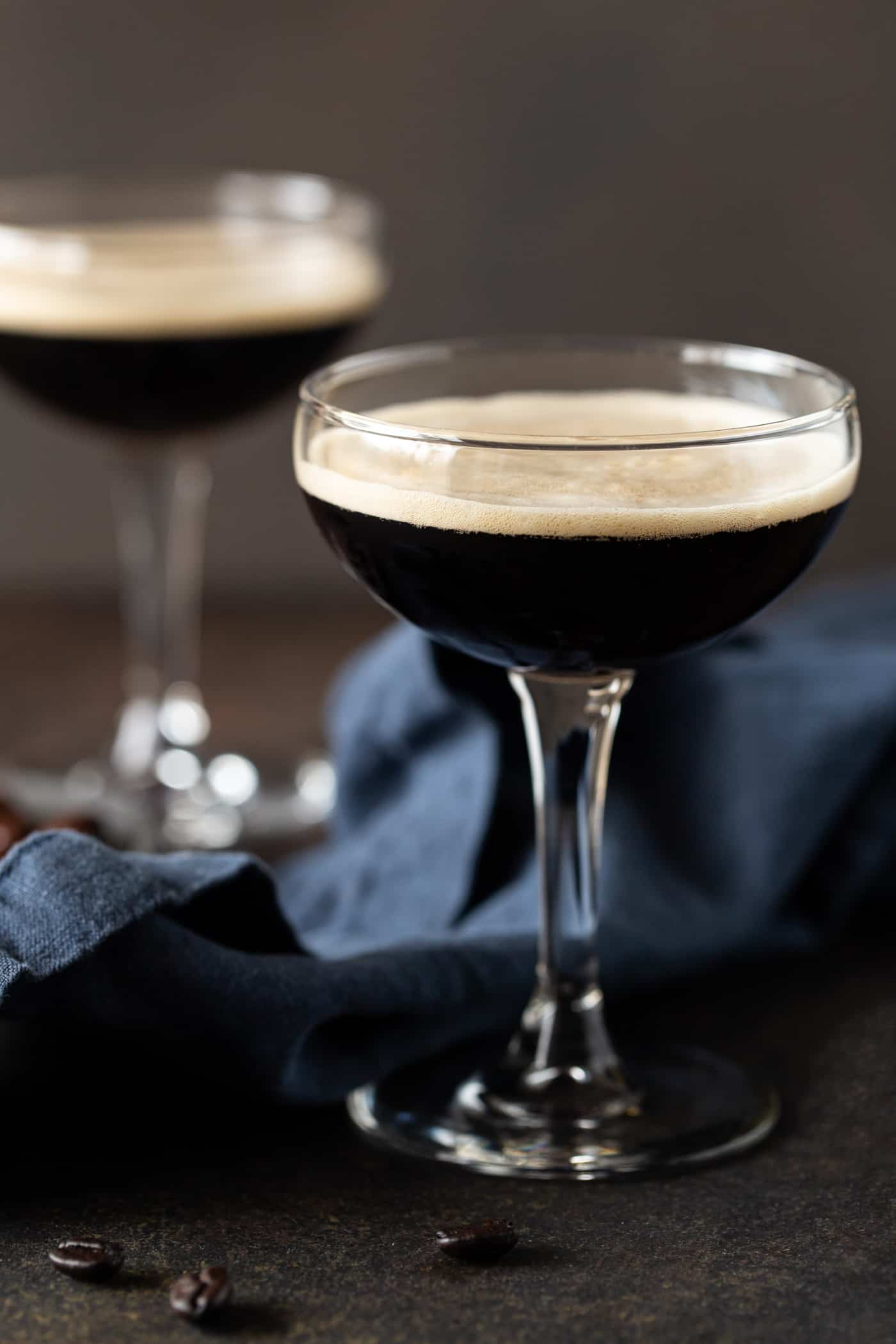 Coffee martinis on a dark background with coffee beans and a navy blue napkin.