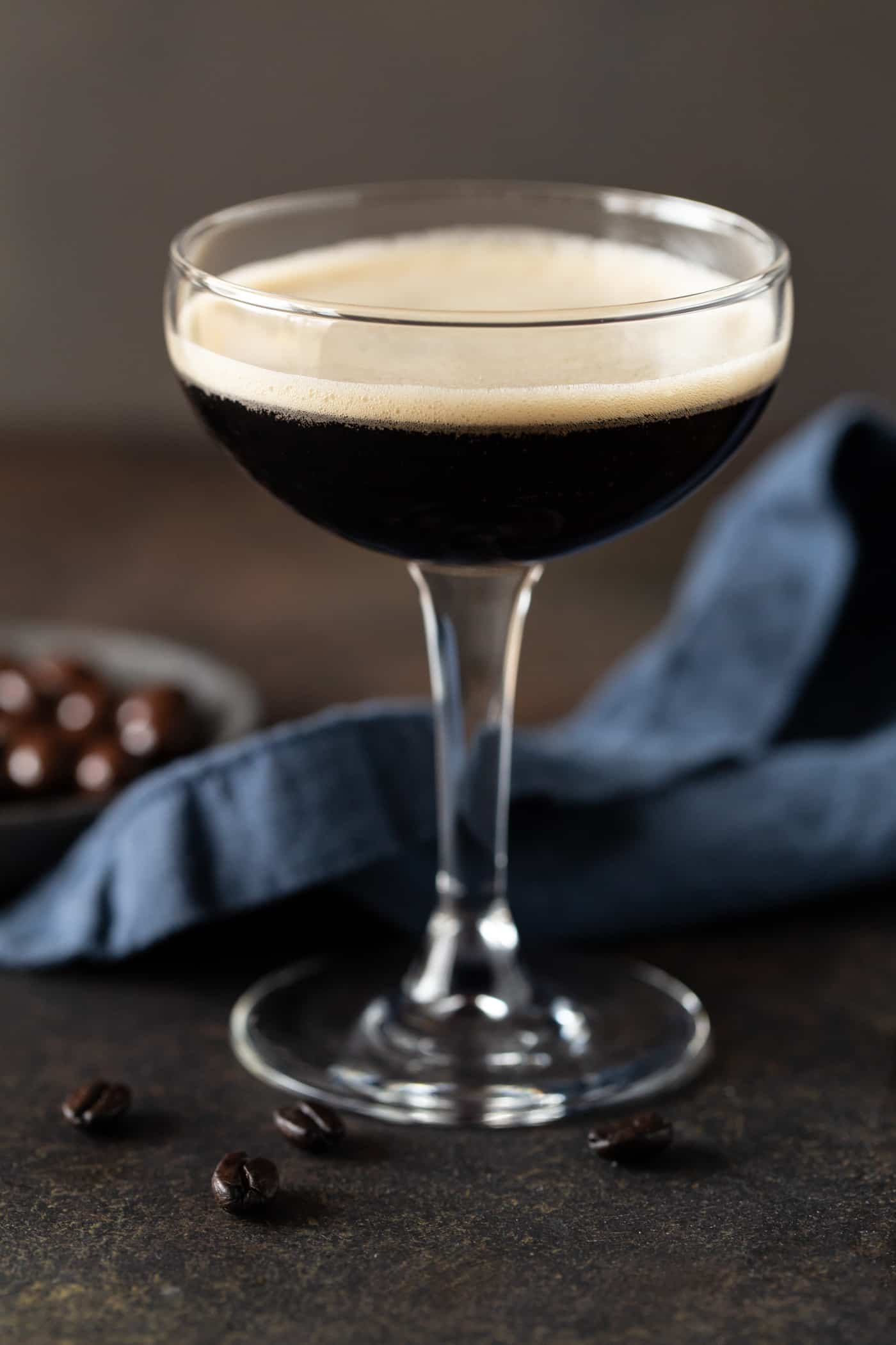 Single Espresso martini with chocolate covered espresso beans and coffee beans for garnish on a dark background.