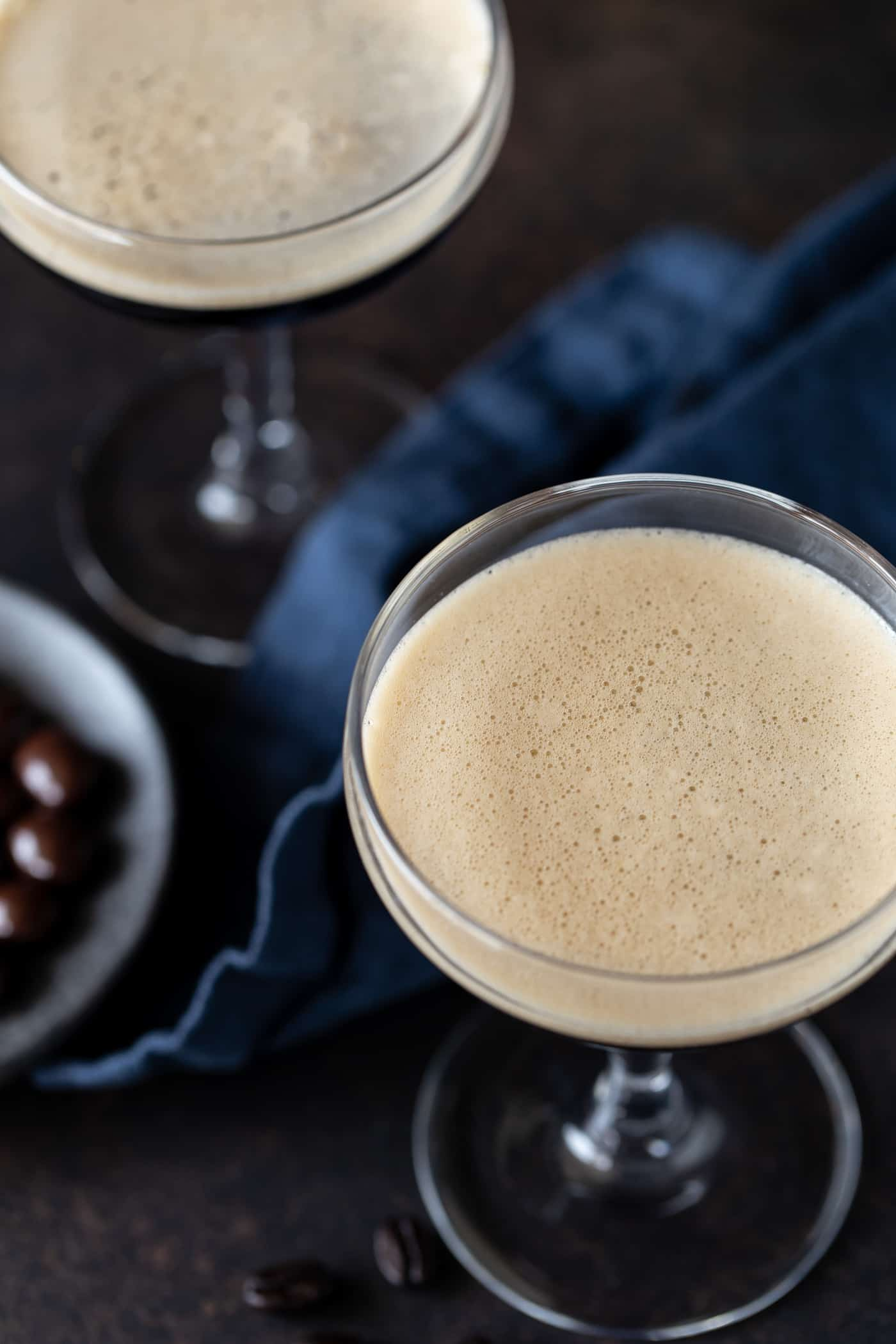 Top down image of two martini glasses with frothy tops on a dark background with a navy blue linen napkin.