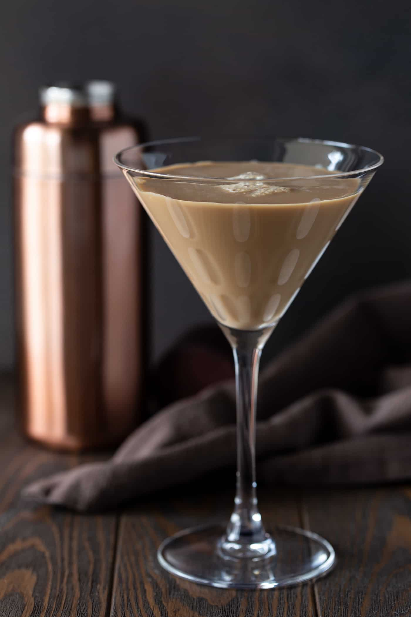 Kahlua Chocolate Martini is a tall martini glass with a rose gold shaker in the background.
