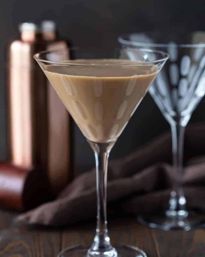 2 martini glasses on a dark surface with a rose gold martini shaker in the background. Front martini glass is filled with kahlua chocolate martini