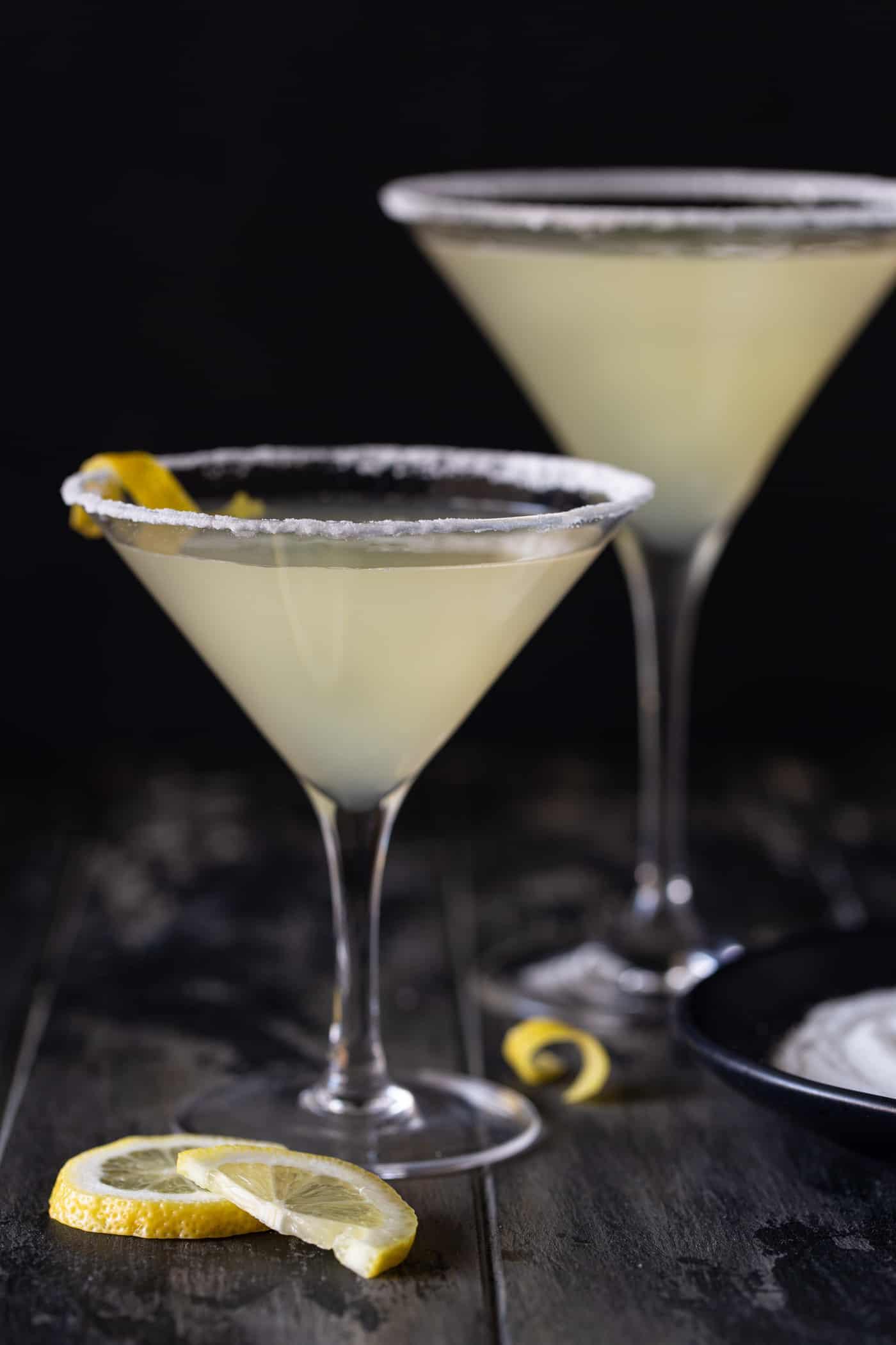 Lemon drop martinis in glasses with lemon twists for garnish.