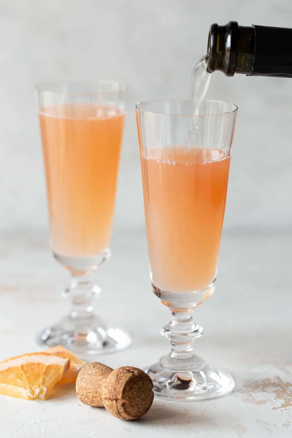 2 champagne flutes filled with mimosa on a white background.