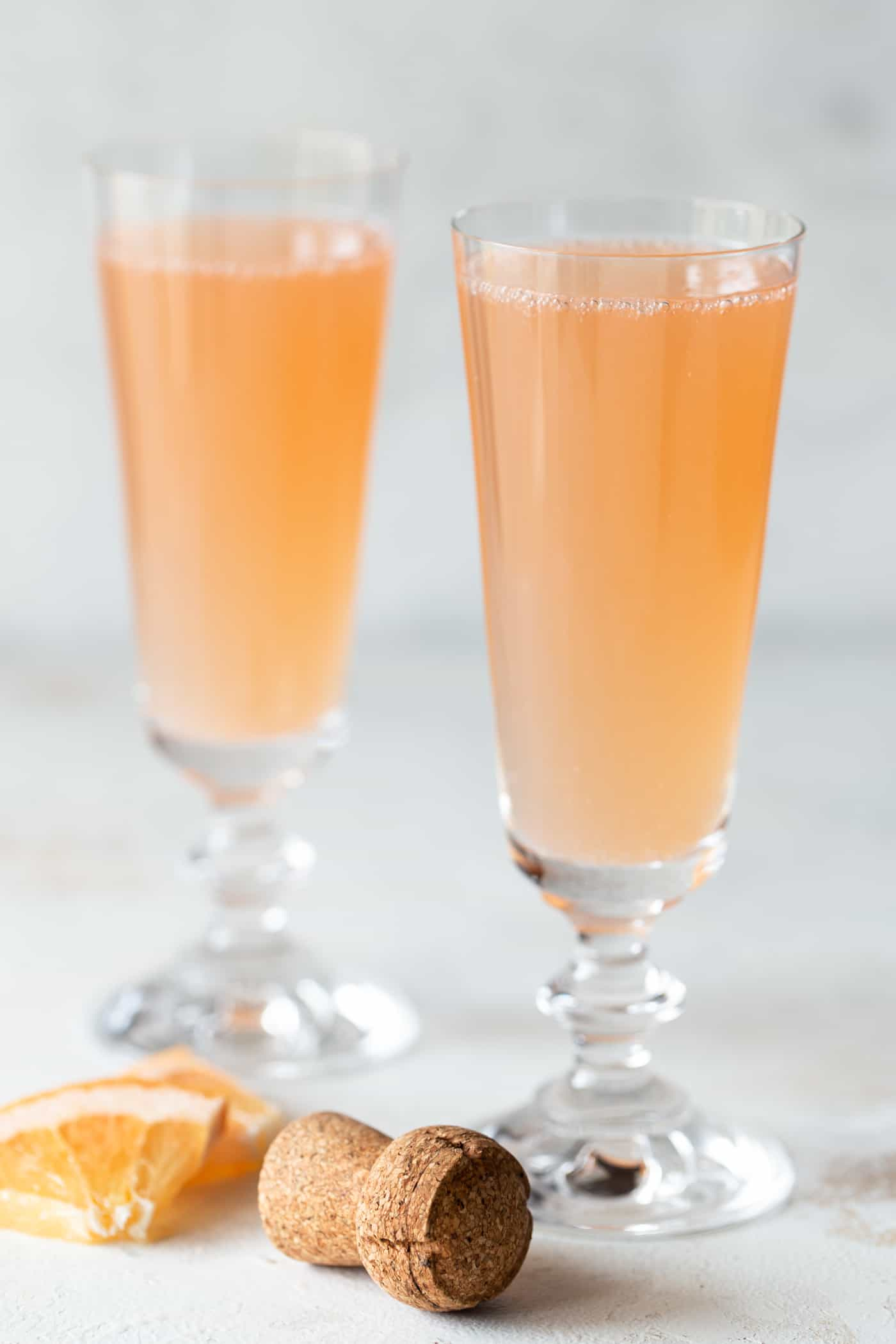 2 mimosas in champagne flutes with fresh grapefruit chunks for garnish.