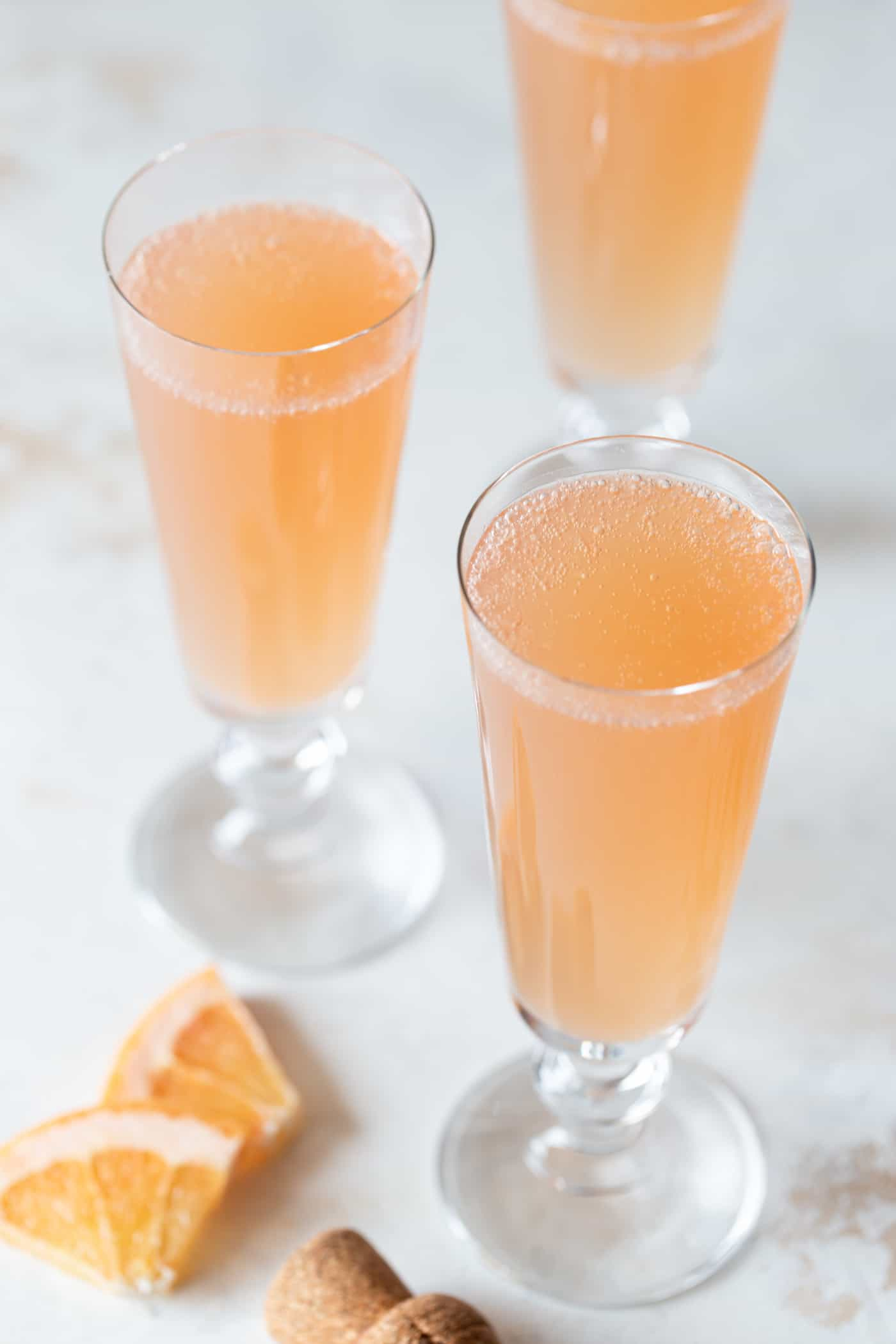 3/4 image of grapefruit mimosas in champagne flutes garnished with fresh grapefruit on a white background.